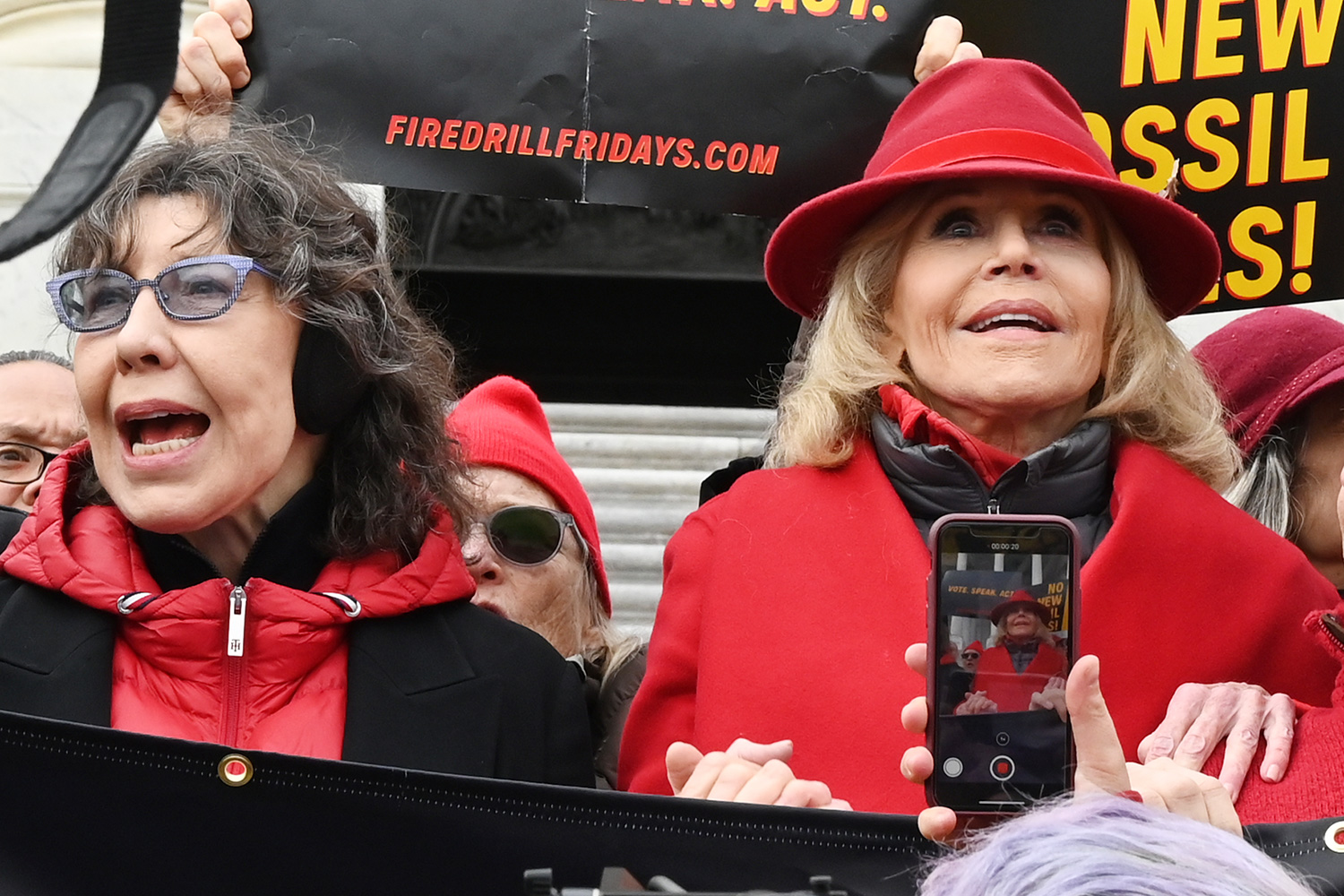 Actresses and activists Lily Tomlin (L) and Jane Fonda hold hands as they lead a climate protest on the steps of the US Capitol in Washington, DC on December 27, 2019. - The rally marked the 12th consecutive Friday that Jane Fonda has led protests in Washington, DC. The protests call for an end to new fossil fuel exploration while this week's demonstration focused on the impact of climate change on the world's forests.