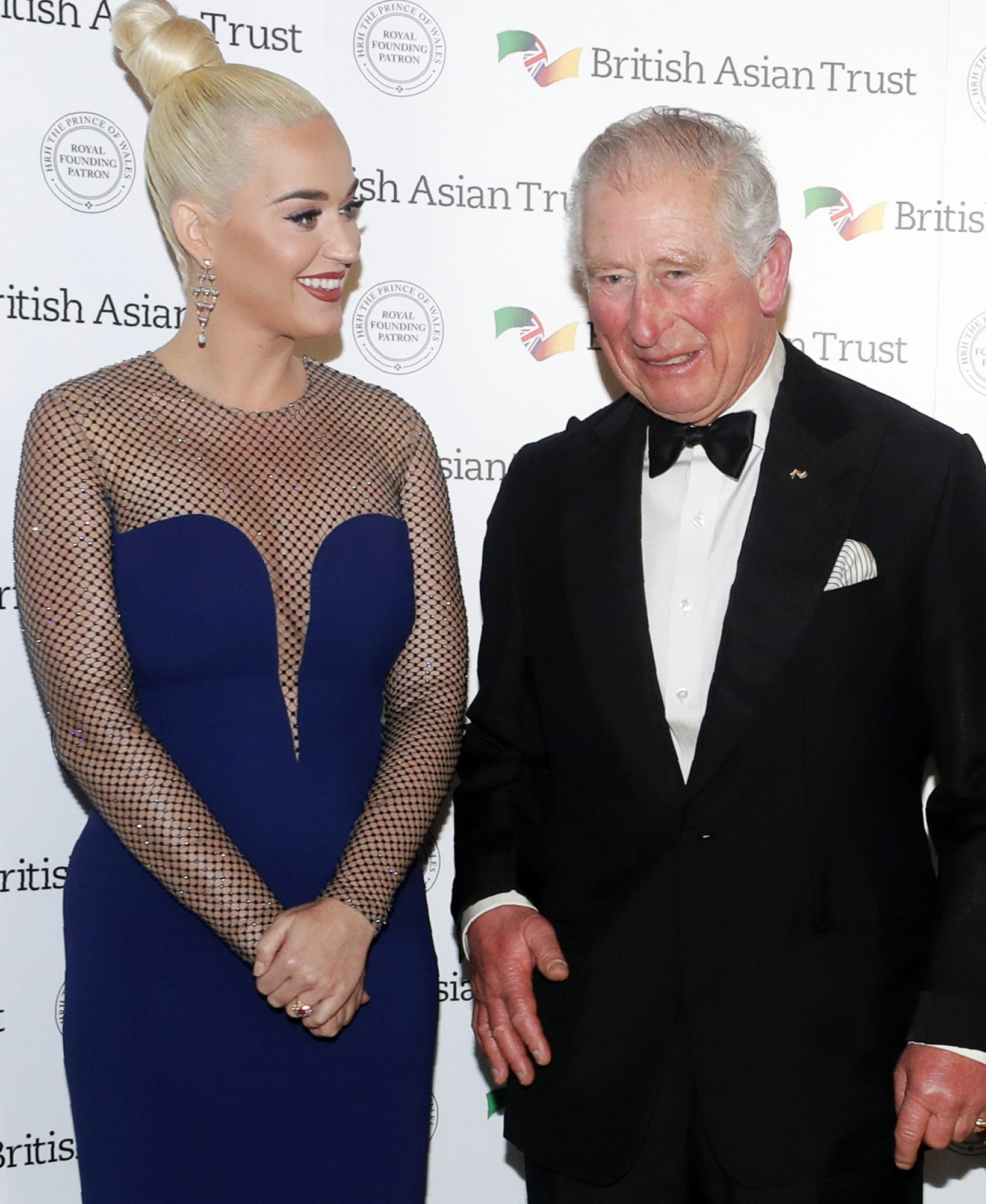 Prince Charles, Prince of Wales, Royal Founding Patron of the British Asian Trust poses with musician Katy Perry