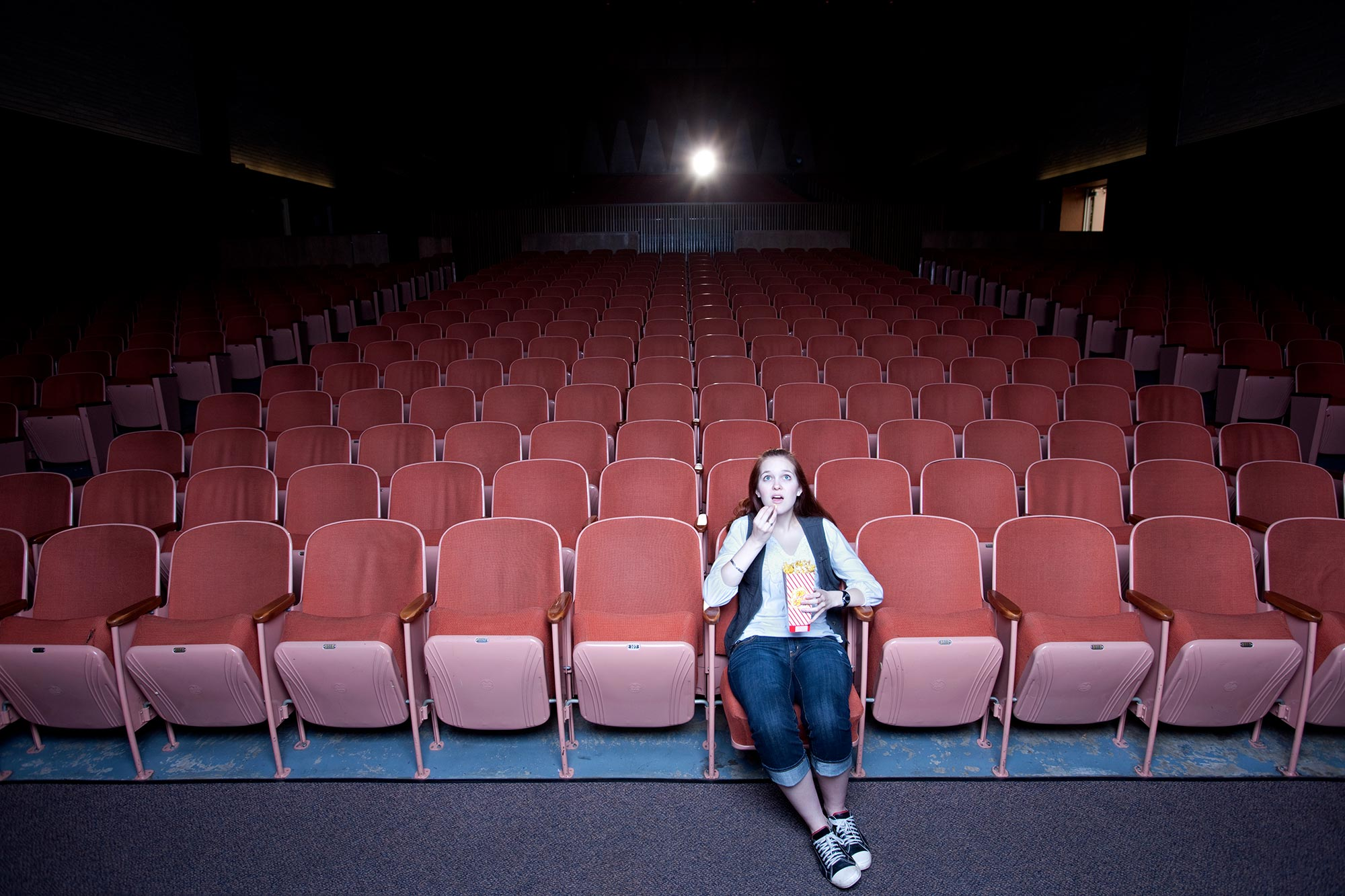 Woman watching movie alone in a theater