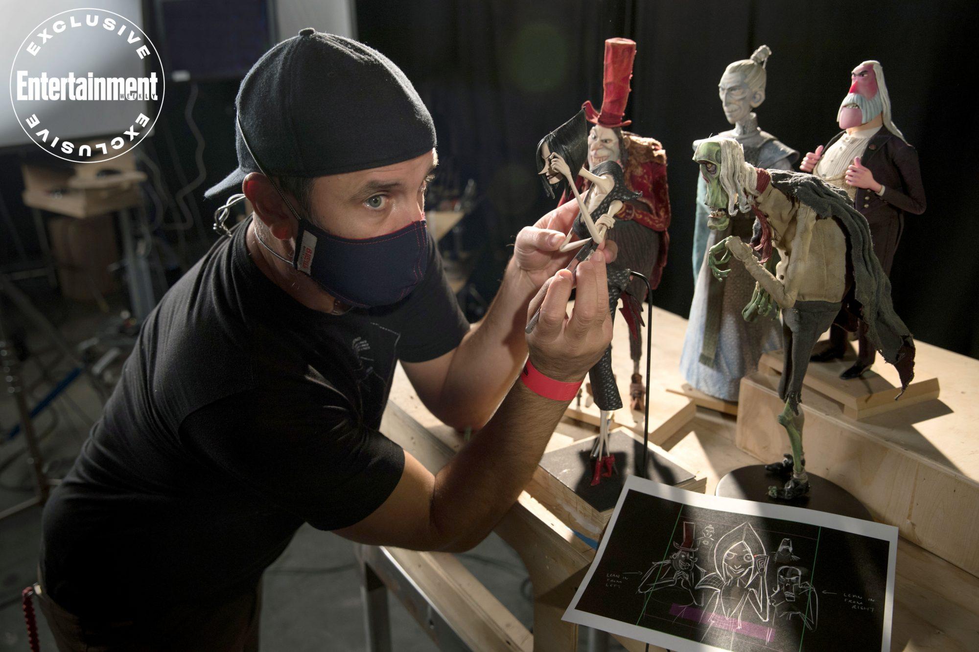 Masked animator posing puppets