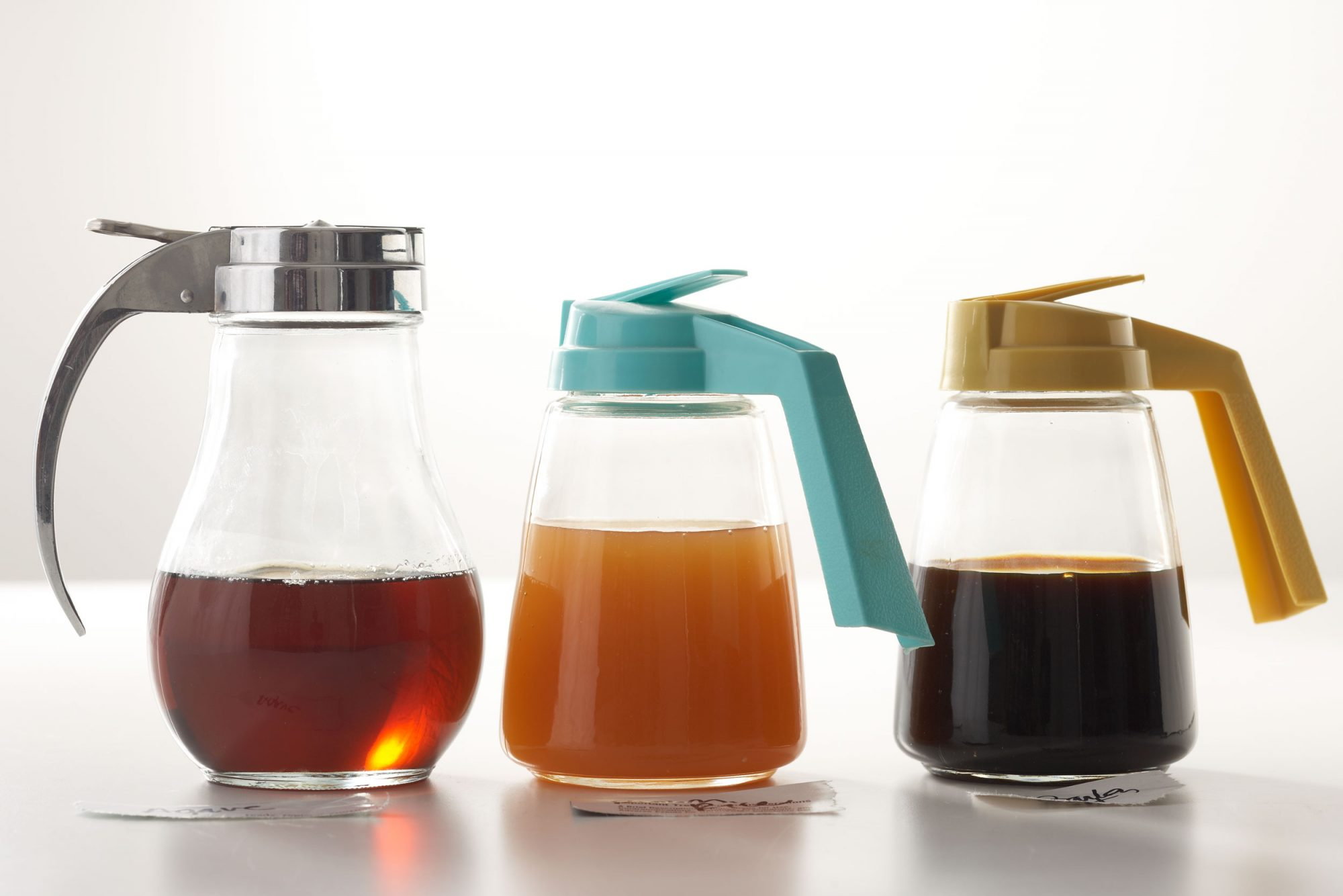 bottles of maple syrup on a white table