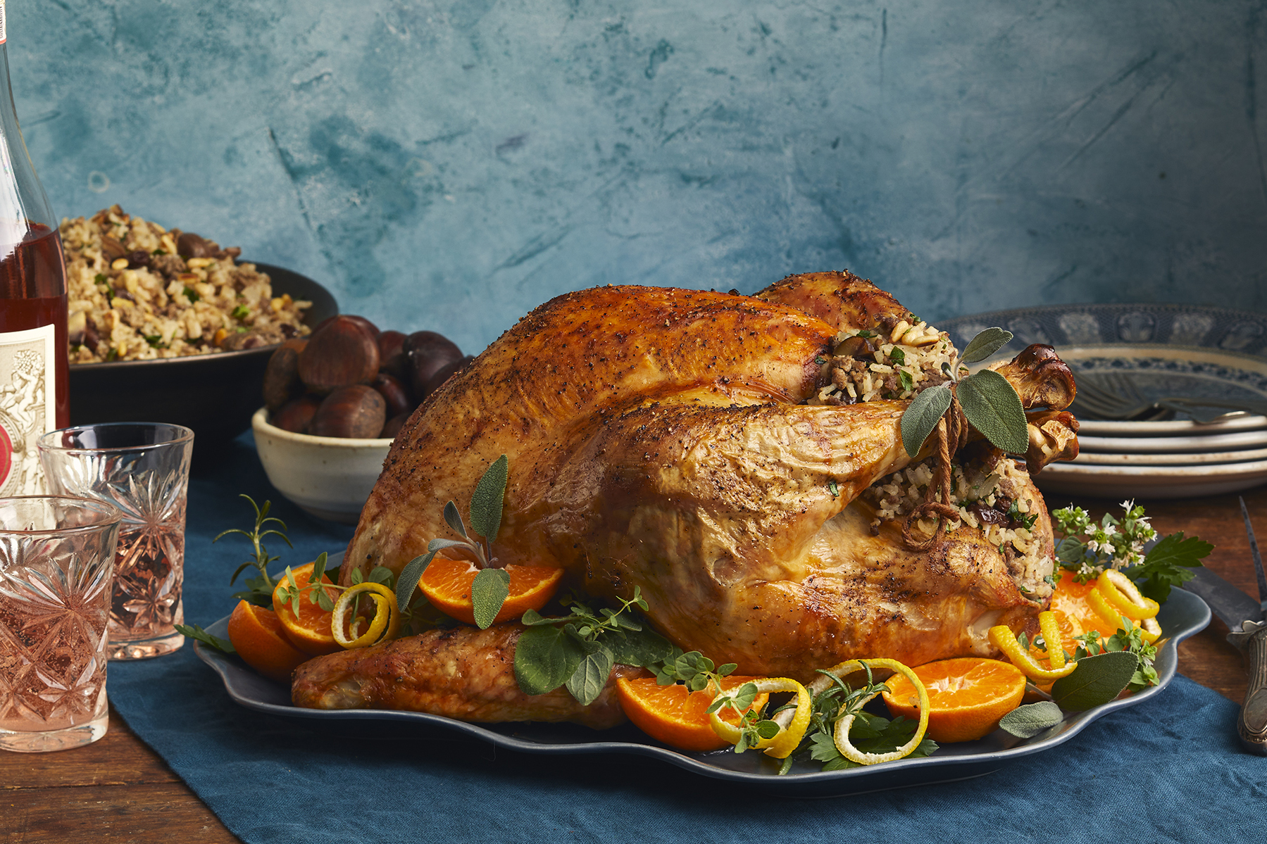 Traditional greek turkey and chestnut stuffing on a silver platter garnished with sliced oranges and fresh herbs.