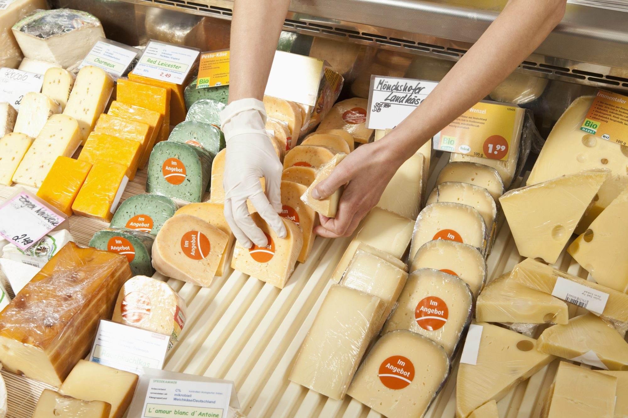 A sale clerk in a cheese shop, focus on hands
