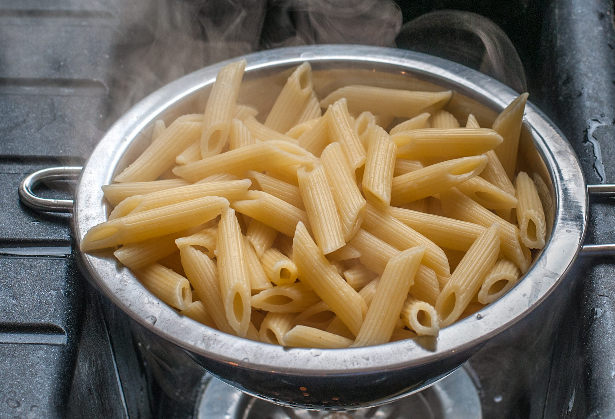 cooked penne rigate pastain a sieve
