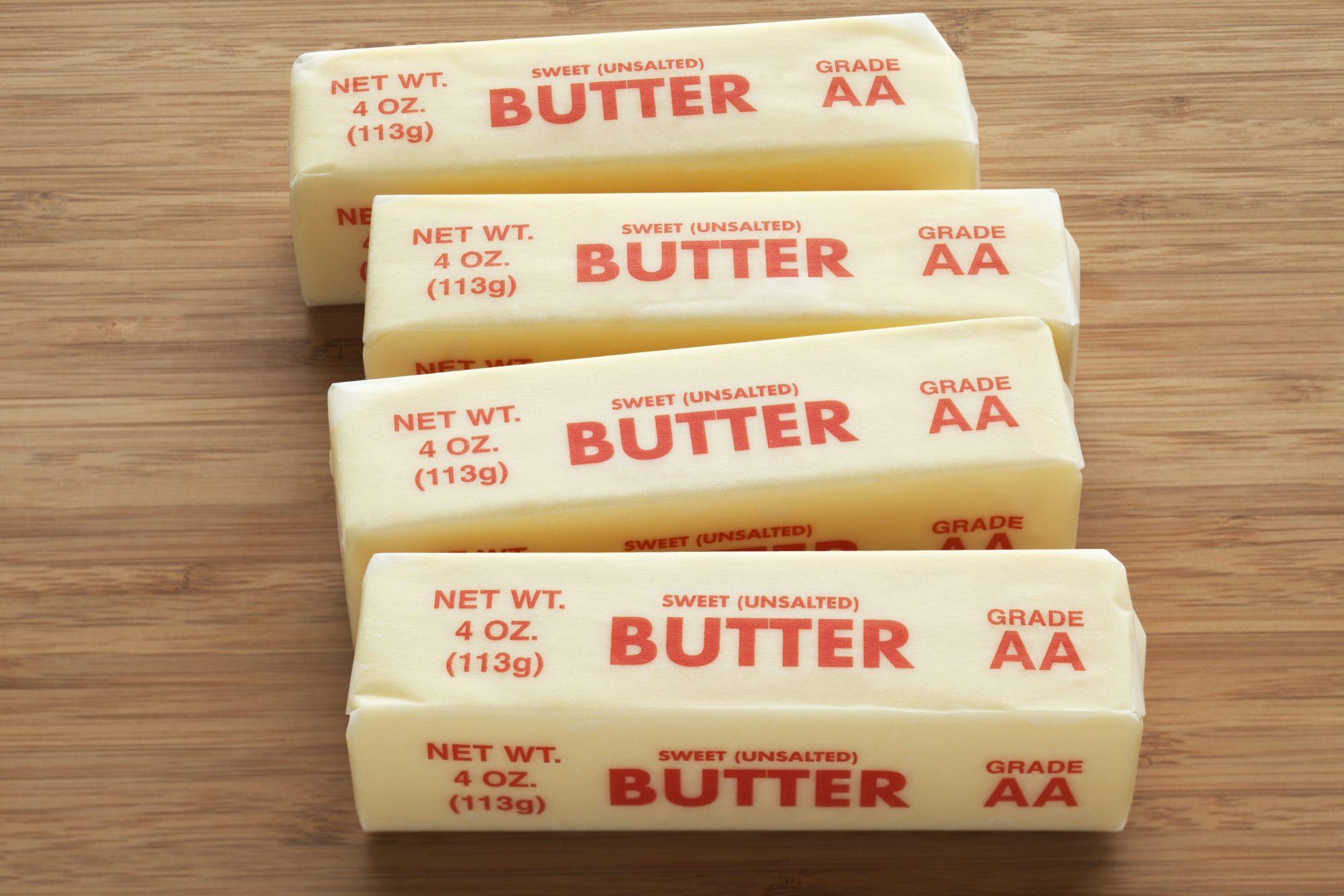 Four sticks of sweet unsalted butter in wrappers