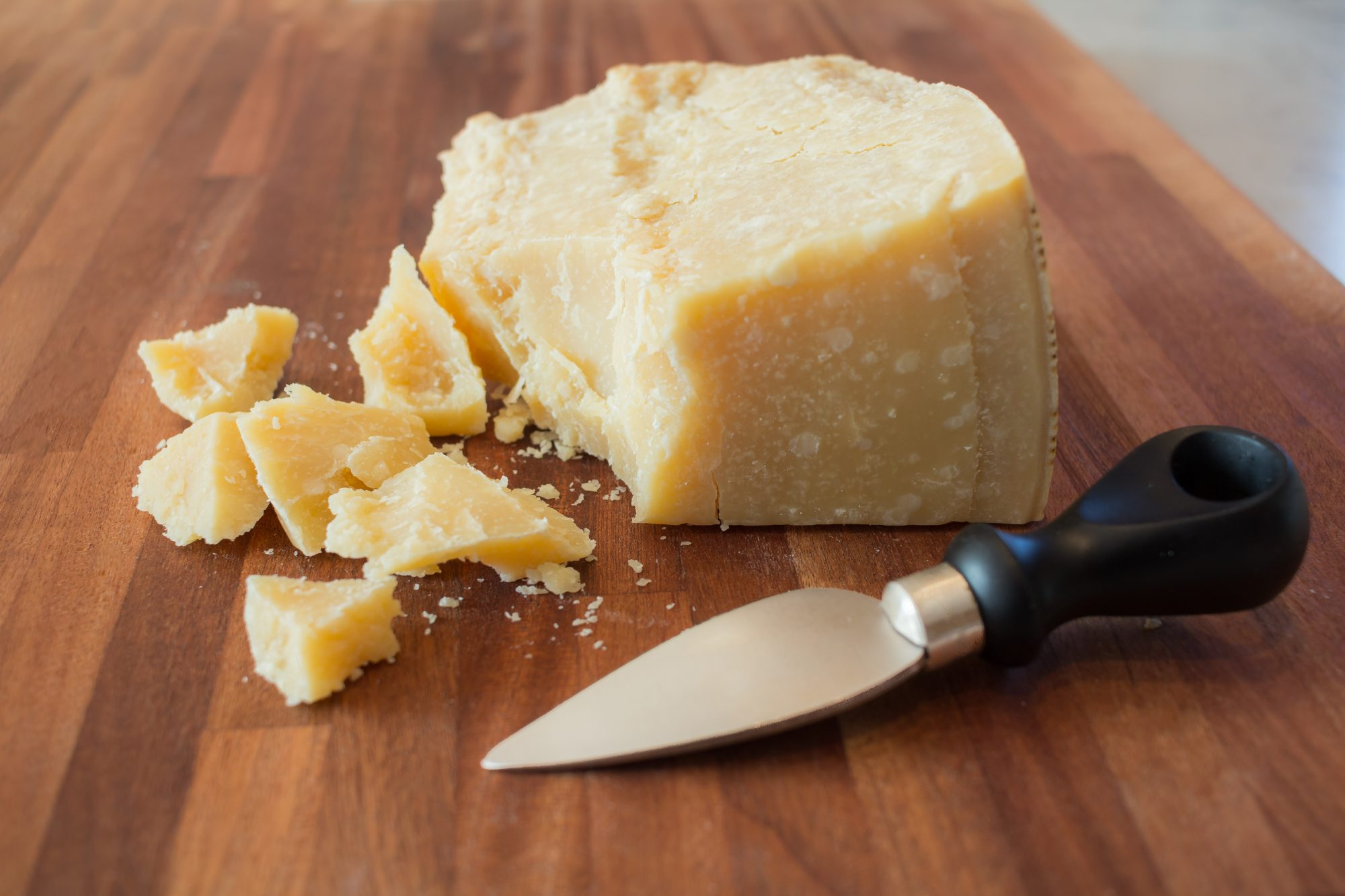 pieces of parmesan cheese on a wooden cutting board