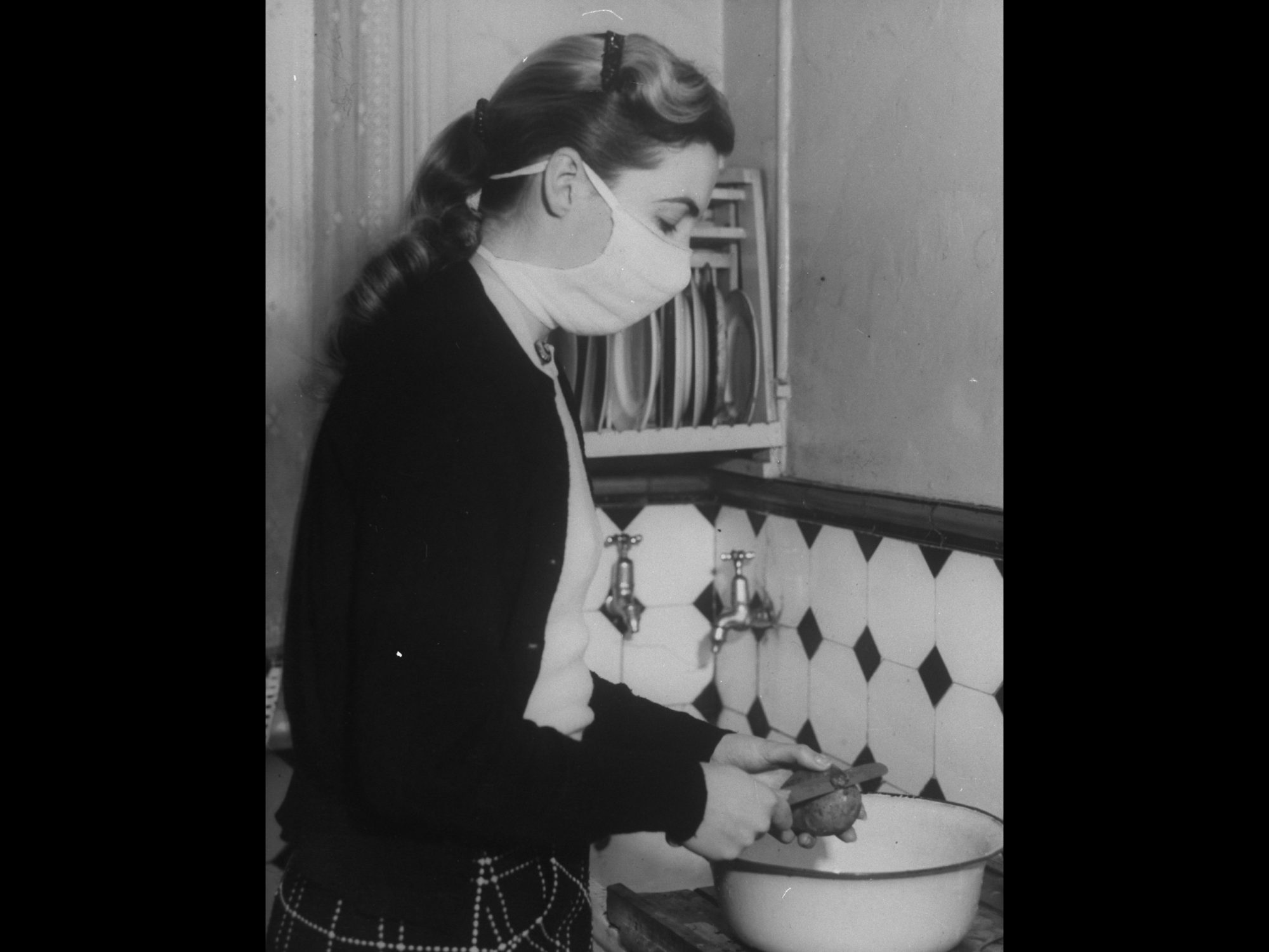 Young woman peeling potato in kitchen with a mask on
