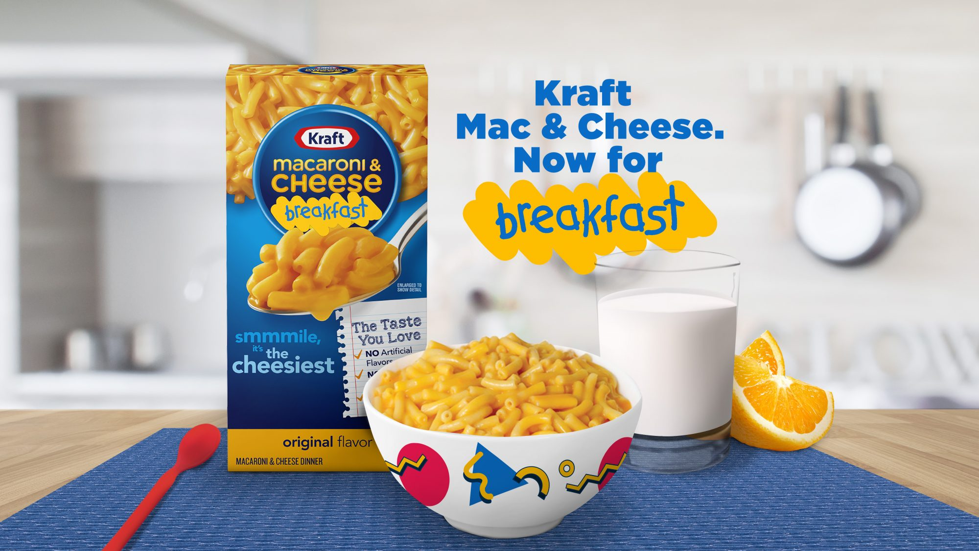 a box of Kraft macaroni and cheese sits behind a bowl of cheesy pasta with a glass of milk and orange slices