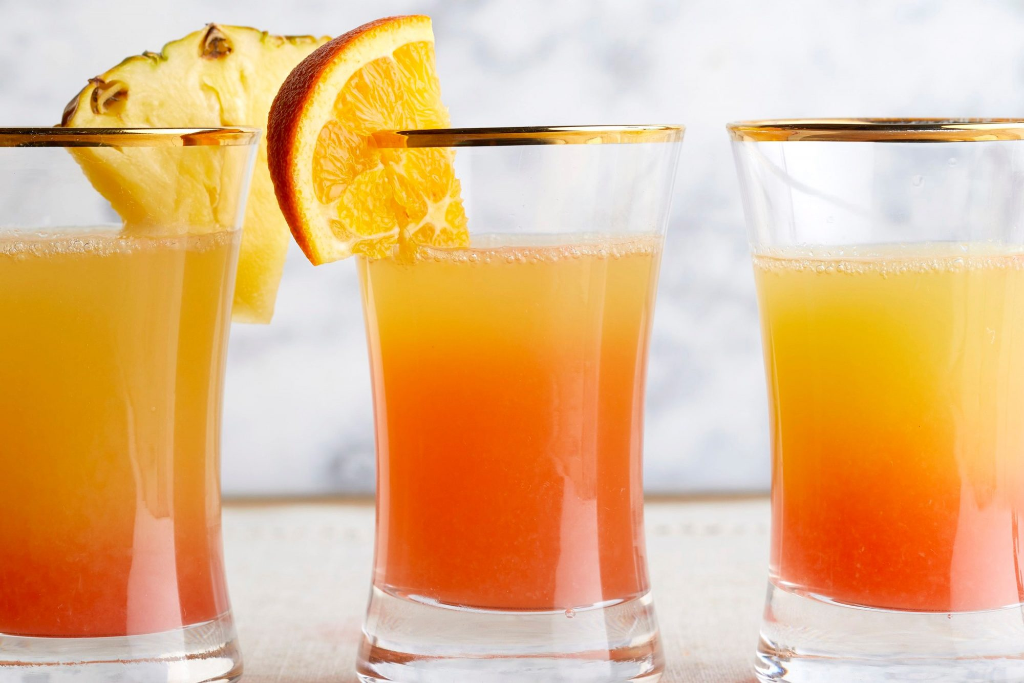 mimosas with orange and pineapple garnishes in short glasses