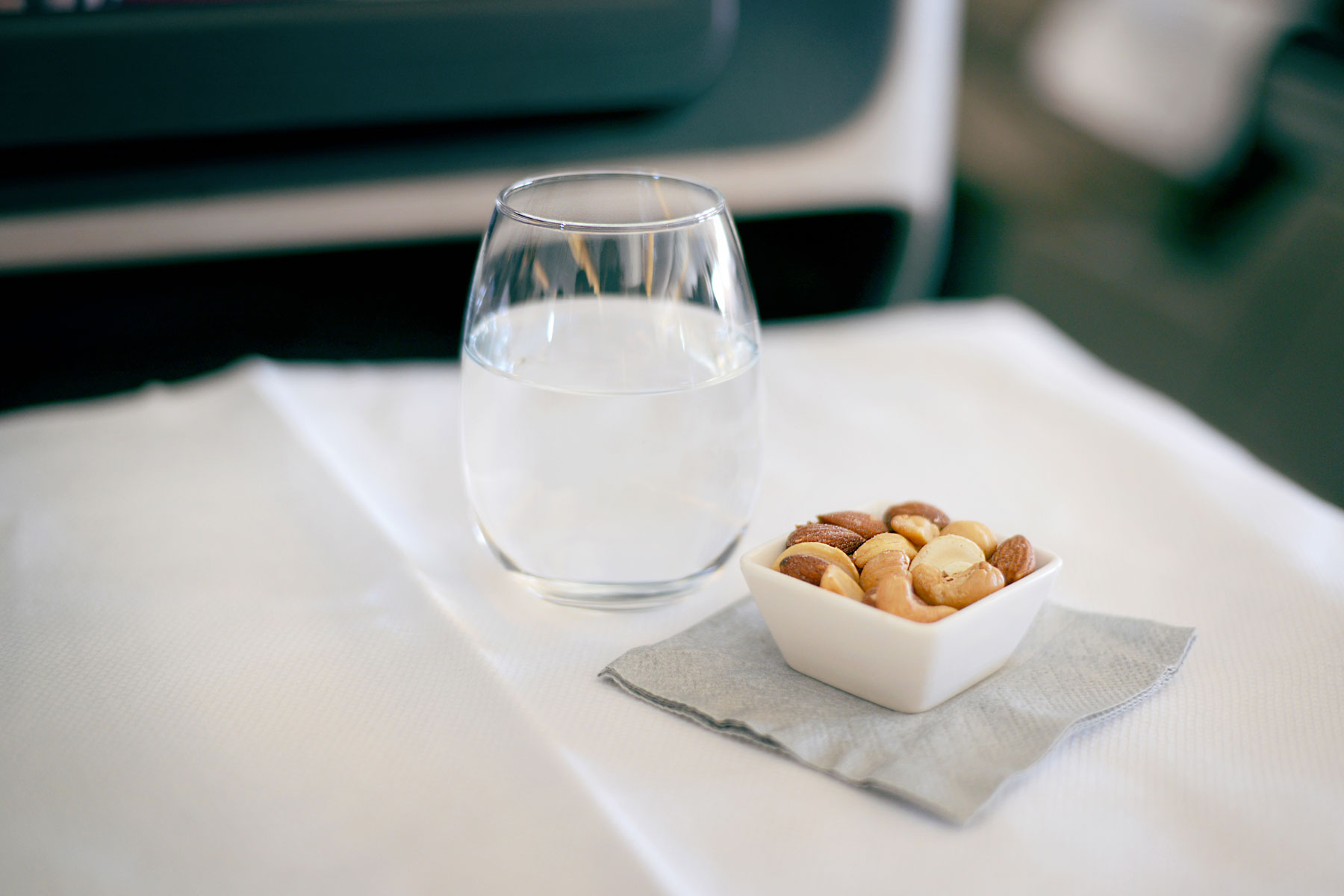 peanuts and a glass of water placed on an airplane seat tray