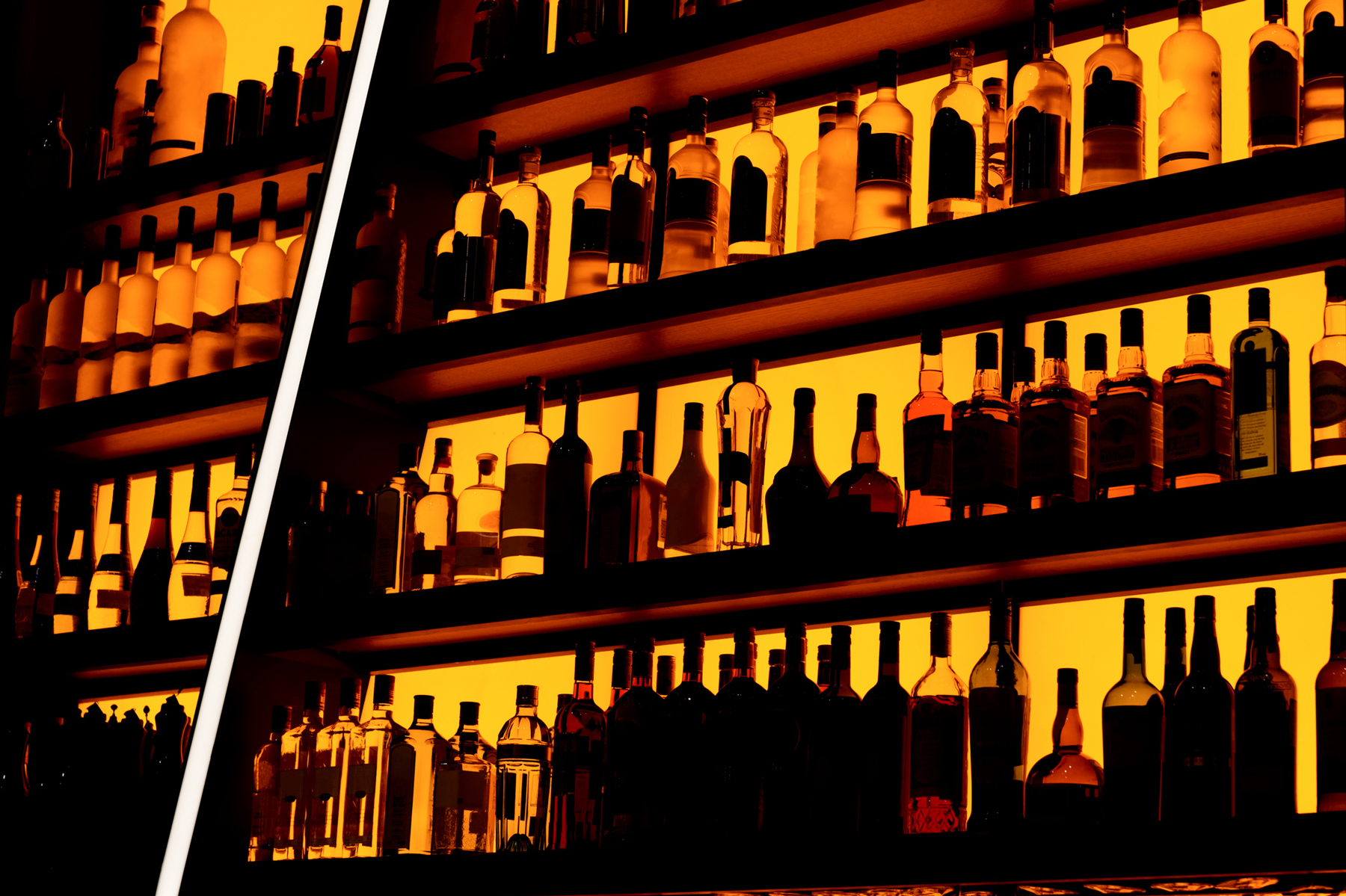 Rows of bottles sitting on shelf in a bar