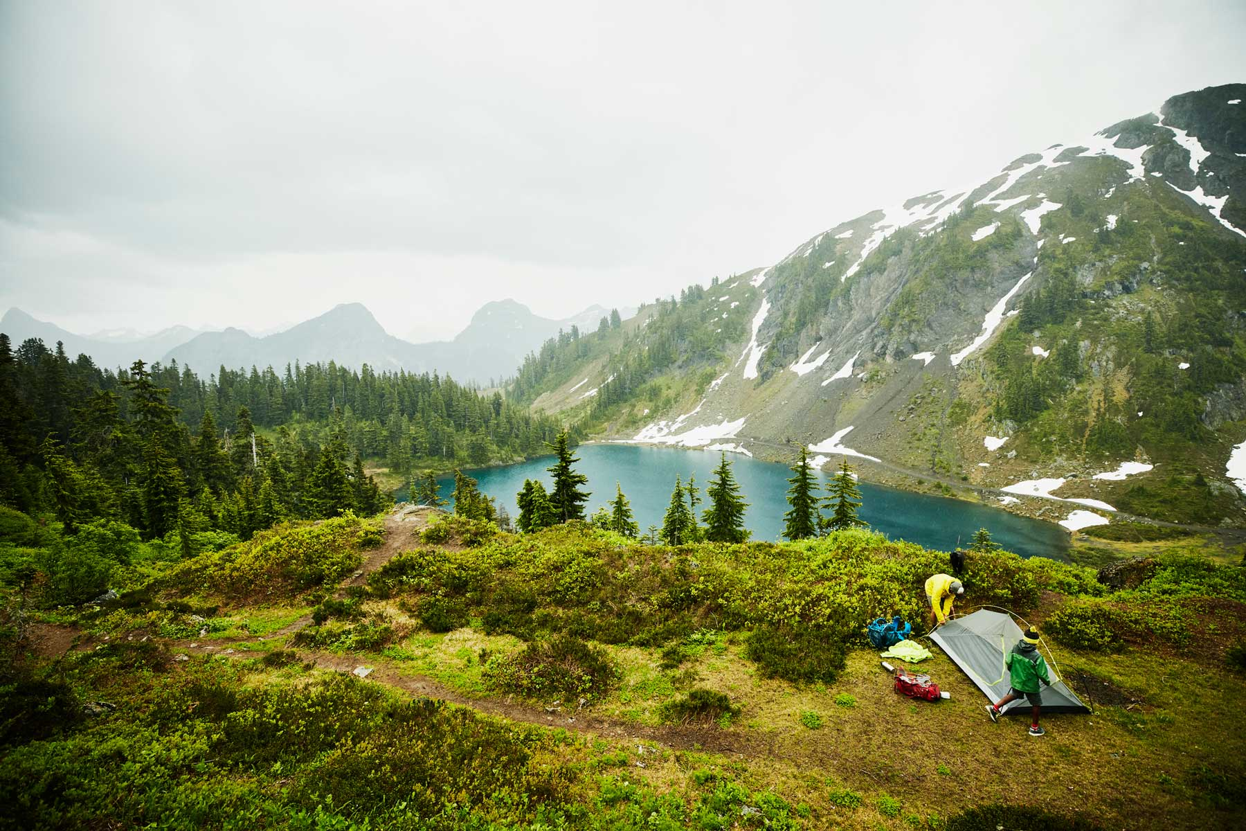 Father and son setting up tent above alpine lake during backpacking trip in rain