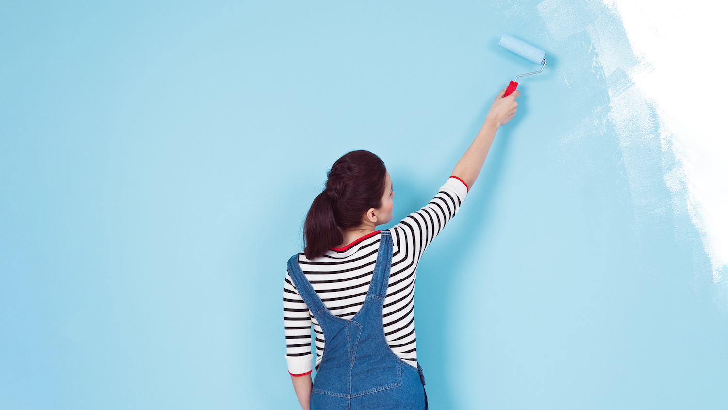 woman painting wall blue