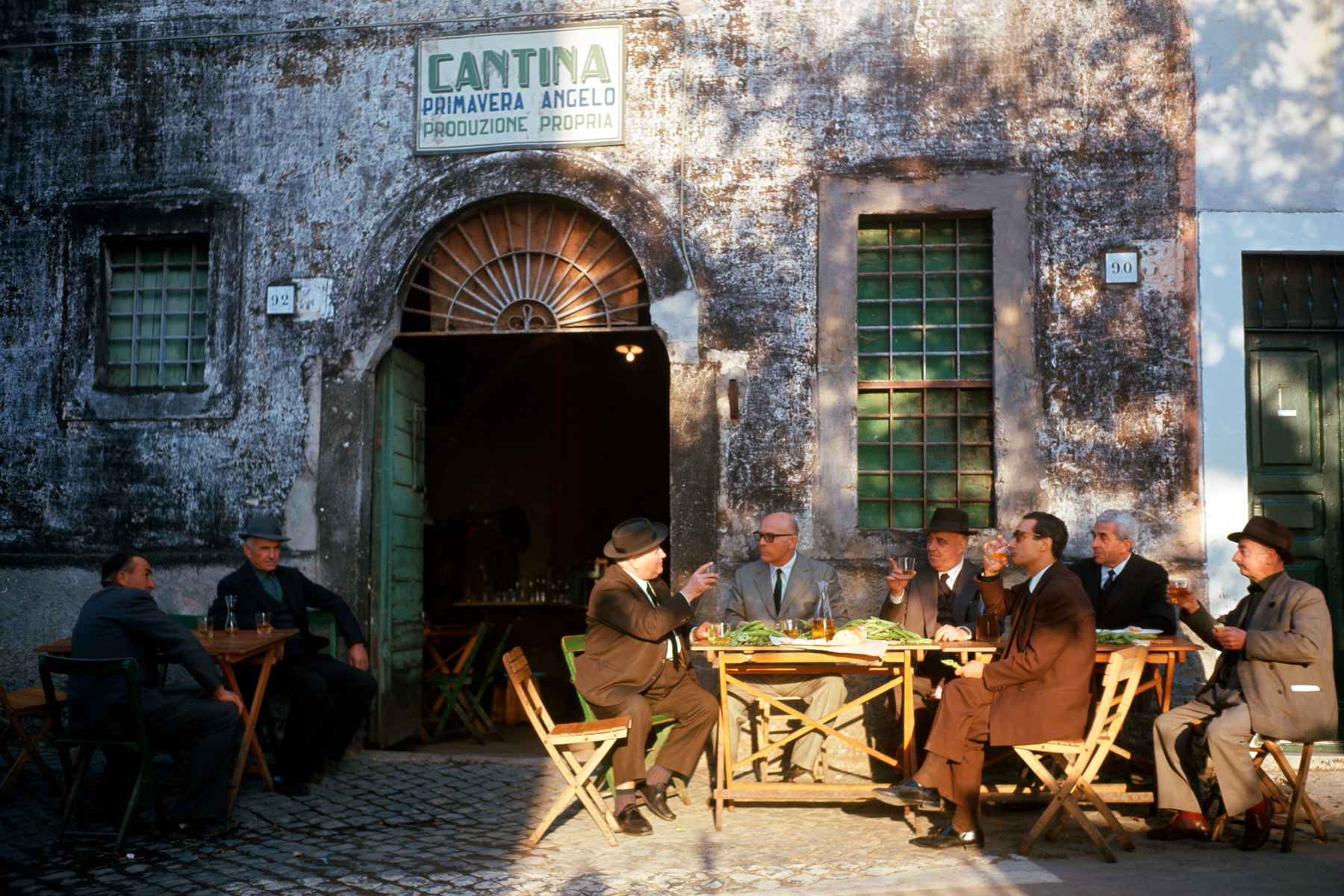 Old people sitting at the tables outside a tavern in Italy