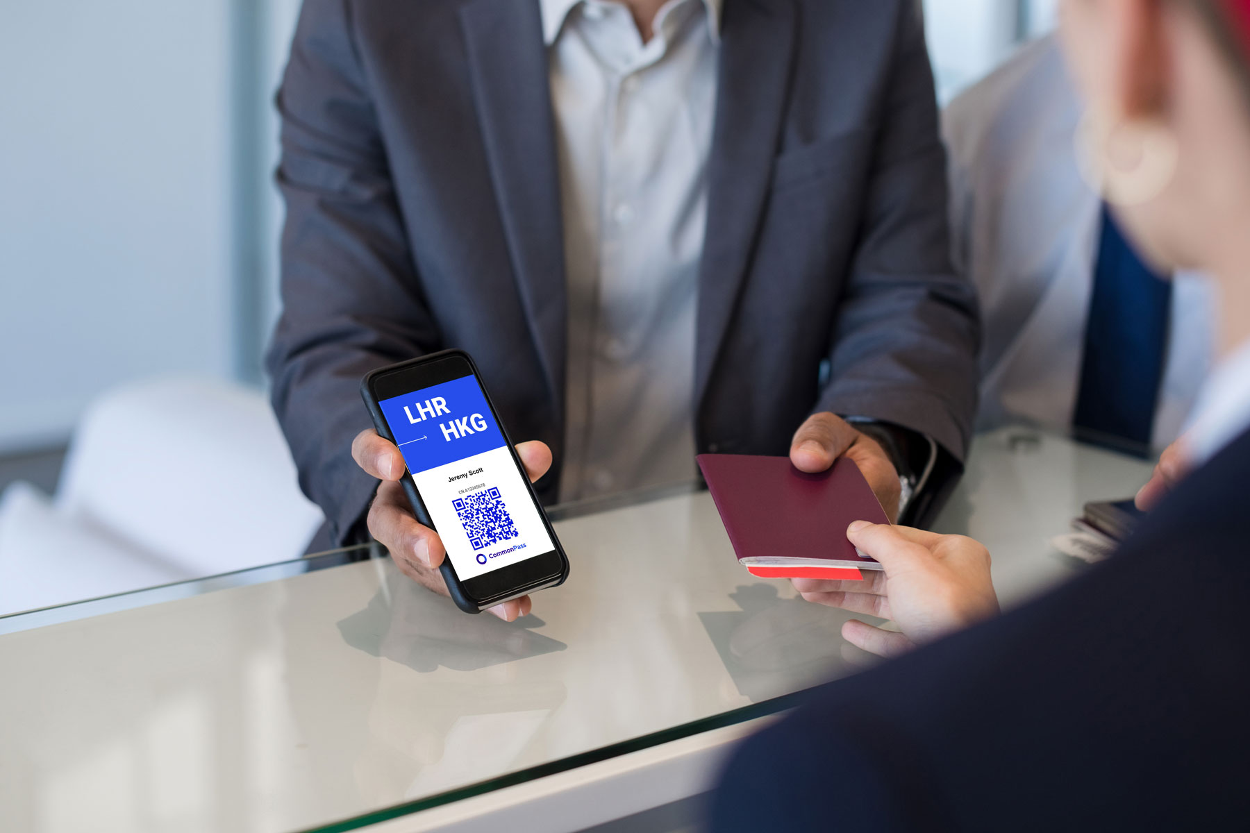 an airport guests holds phone displaying CommonPass App