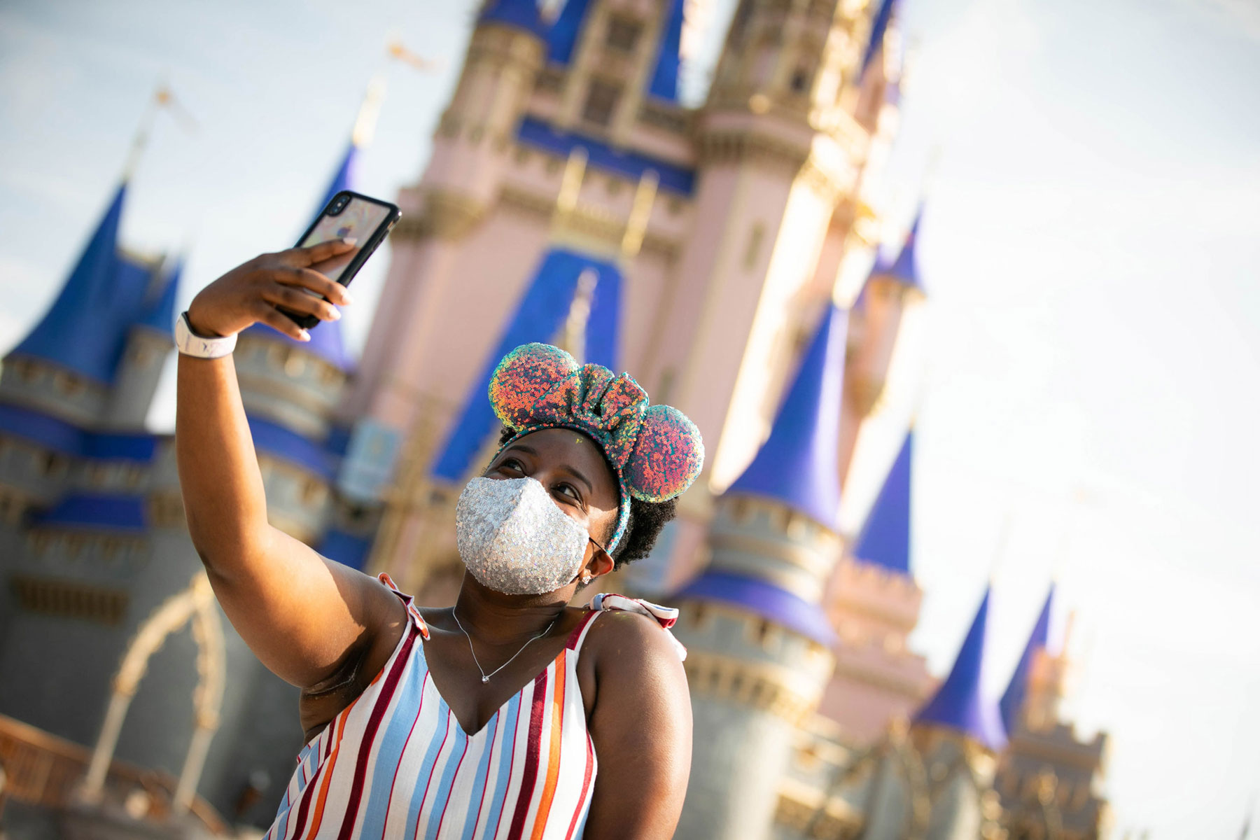 guest at Disney World taking a selfie with a cell phone