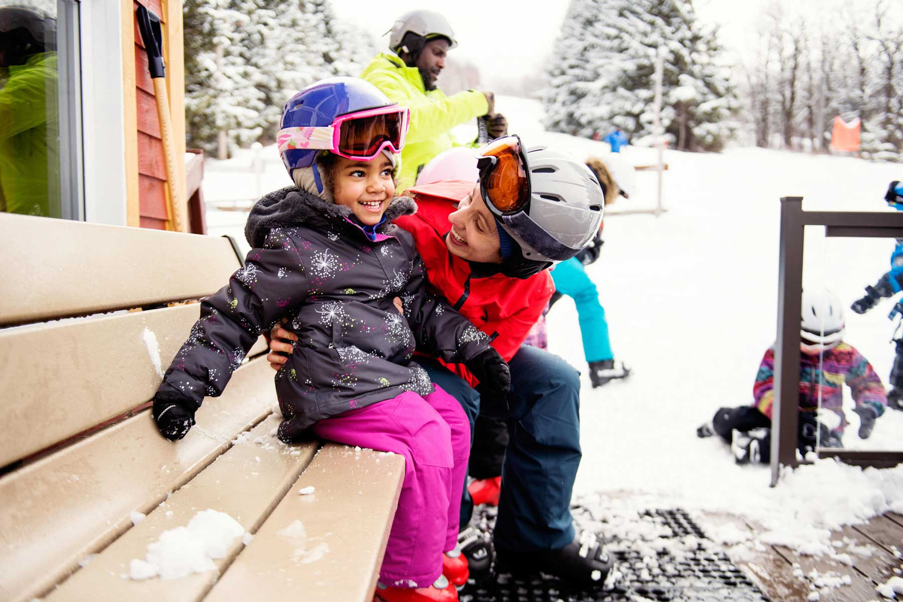 Small child prepares for first time skiing with mother and father