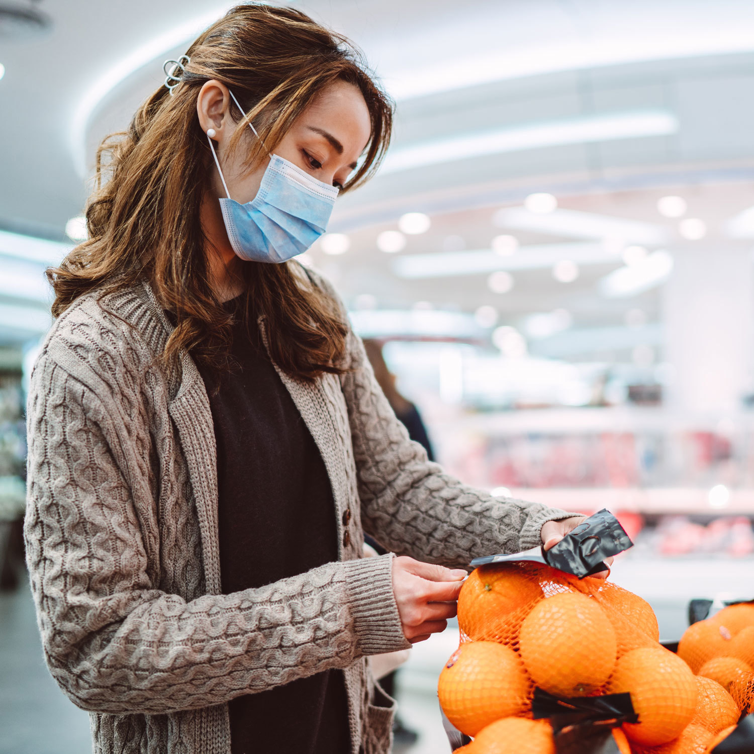 woman wearing a face mask and picking out produce at a grocery store