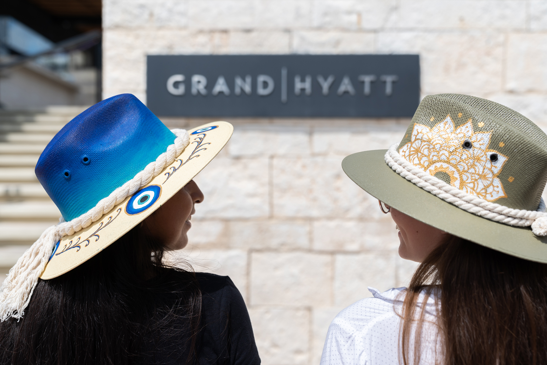 two women wearing handmade painted hats