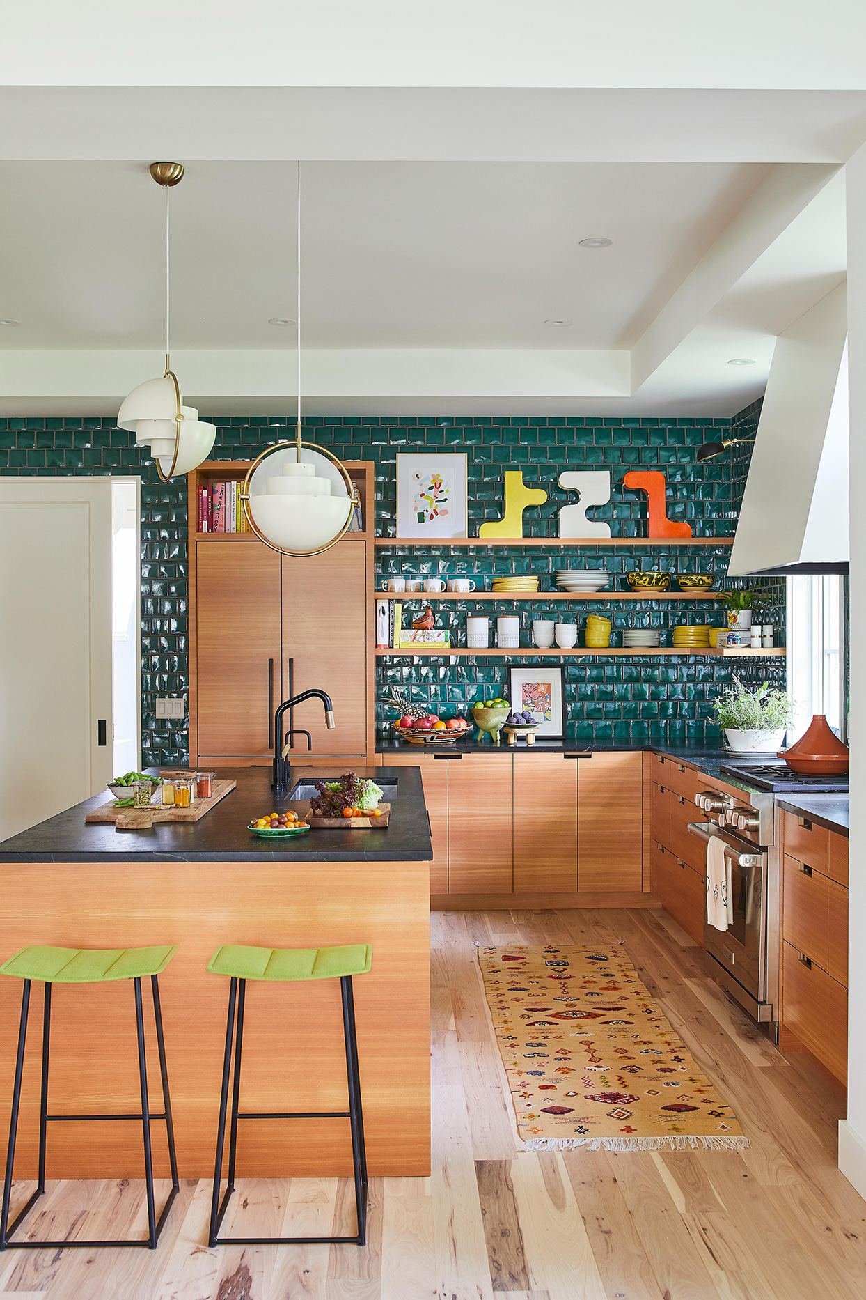 dark green tiled kitchen with larch-wood cabinets with cutout handles