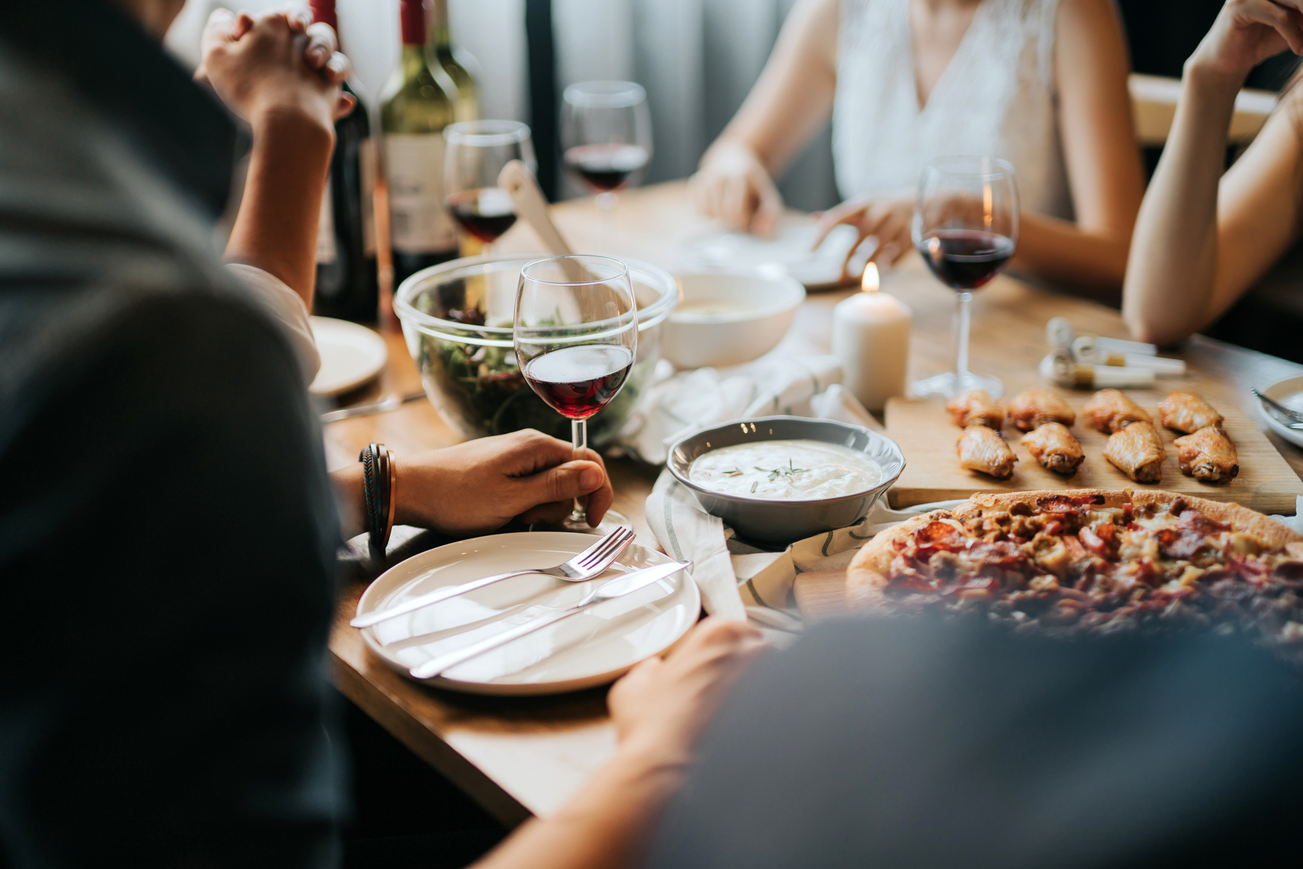 group of people sitting at table with wine glasses and various dinner foods