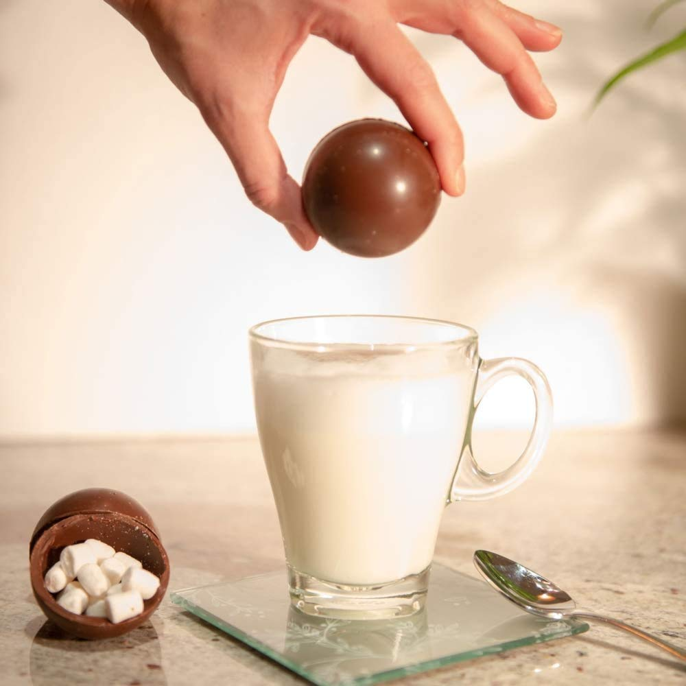 hot chocolate bomb in hand over a mug of milk