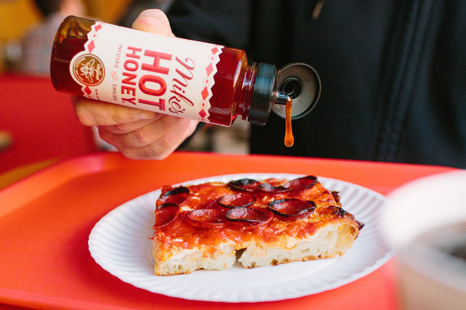 bottle of mike's hot honey getting drizzled on pizza