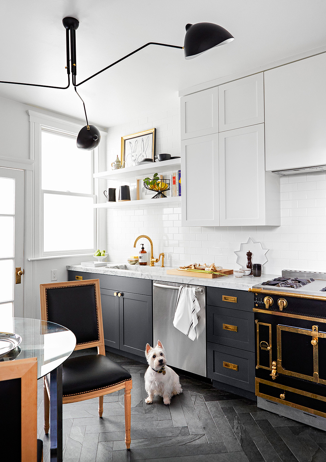 modern kitchen with dark cabinets below and white cabinets above, black and gold oven range
