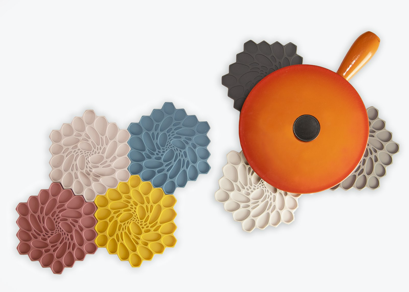 multiple colors of modern-twist Hive Silicone Trivets with a pan on top