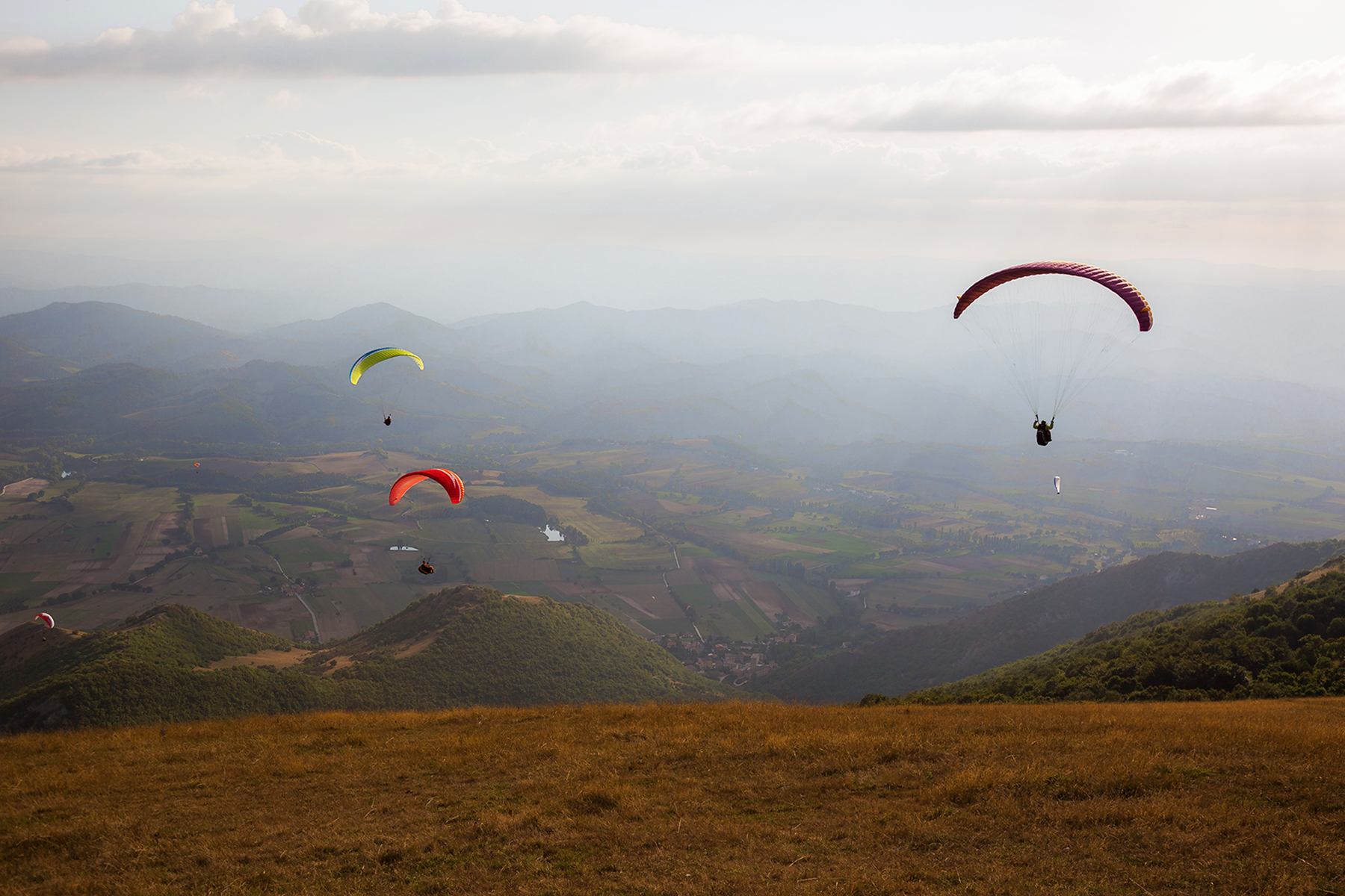 Paragliders flying over a mountain scenery in Umbria
