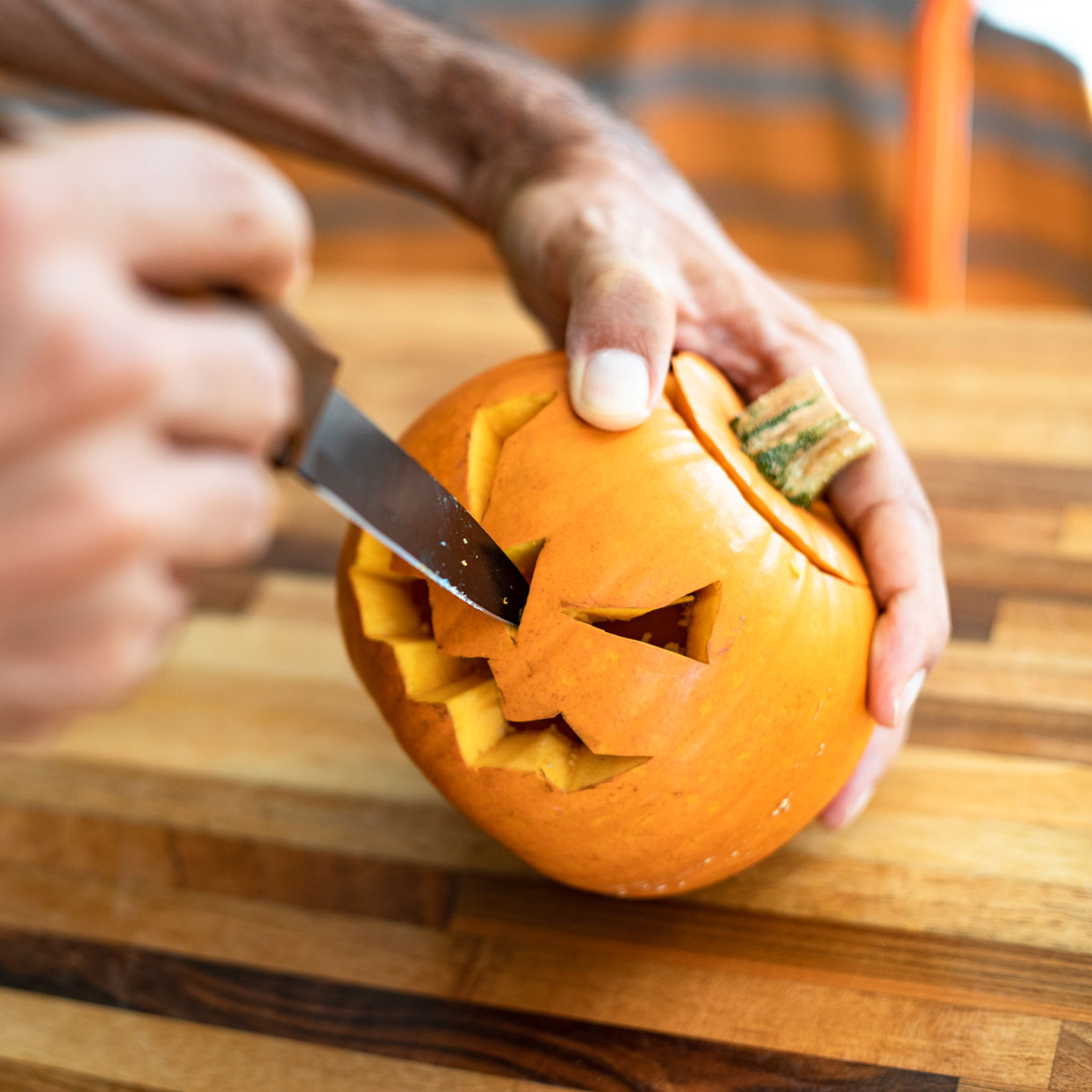 person carving pumpkin with a kitchen knife