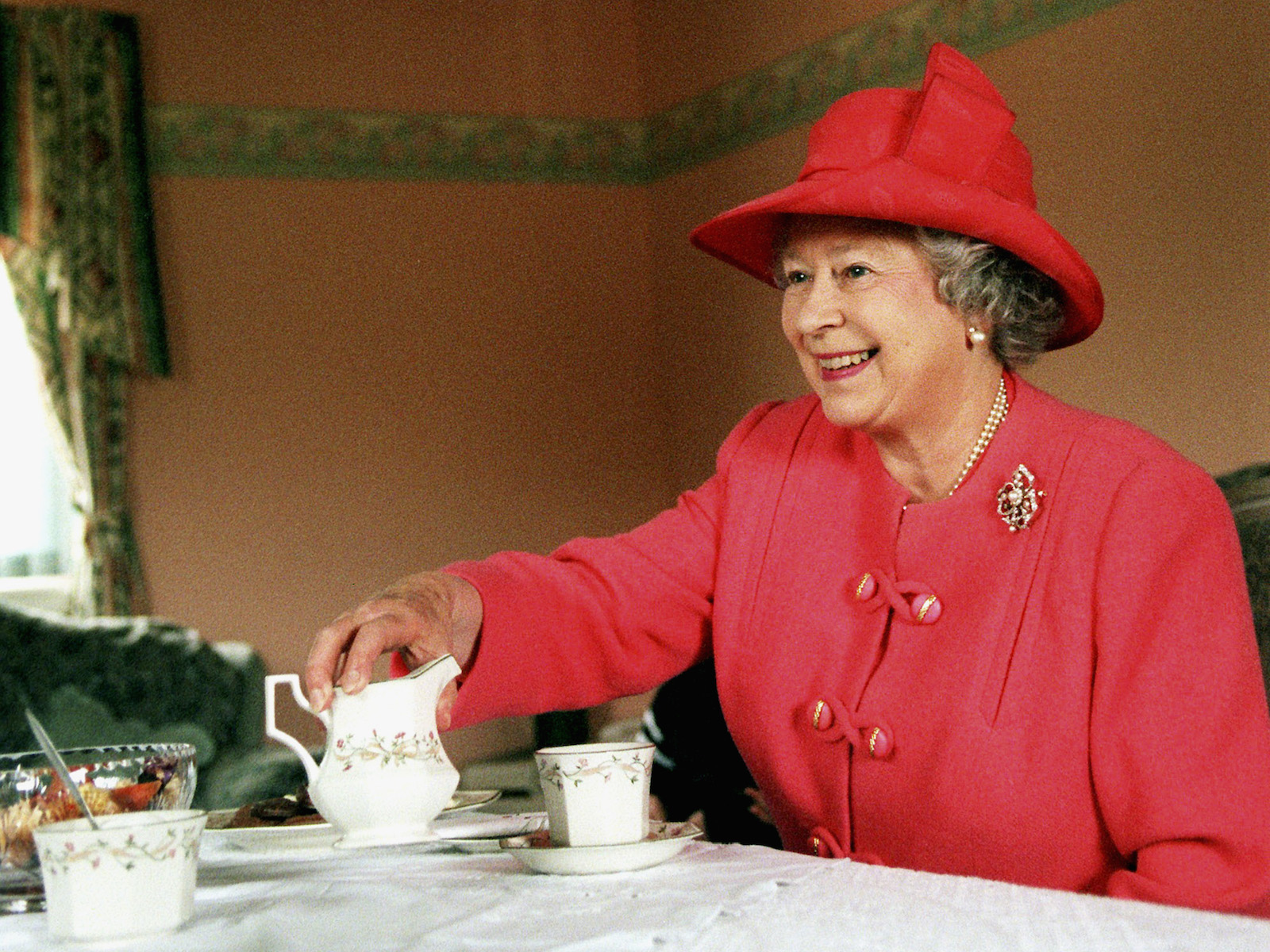 Queen Elizabeth II joins Mrs. Susan McCarron, her ten-year-old son, James, and Housing Manager Liz McGinniss for tea in their home in the Castlemilk area of Glasgow in Scotland on July 7, 1999.