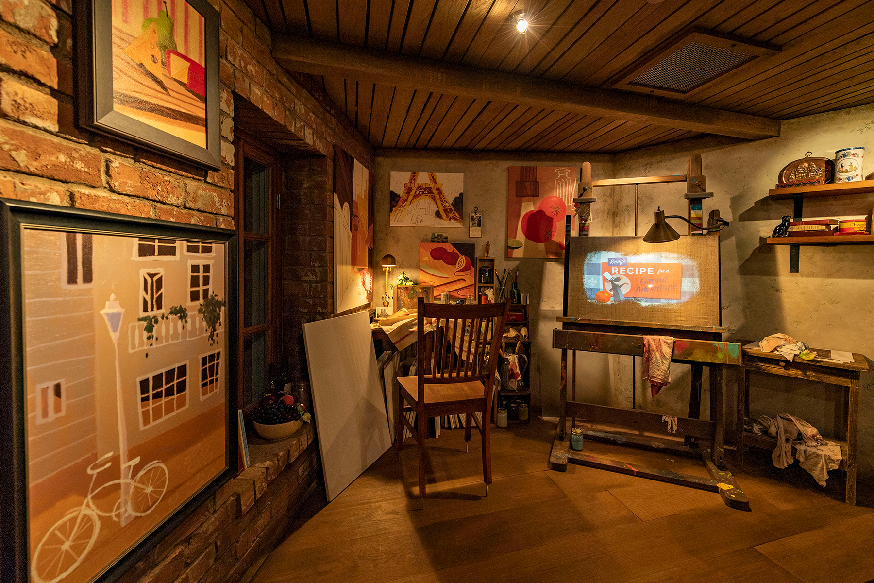 Guests enter a French artist's loft featuring French-inspired paintings, cupboards filled with art supplies and two magical canvases that come to life in the queue for Remy's Ratatouille Adventure in EPCOT at Walt Disney World Resort in Lake Buena Vista, Fla.