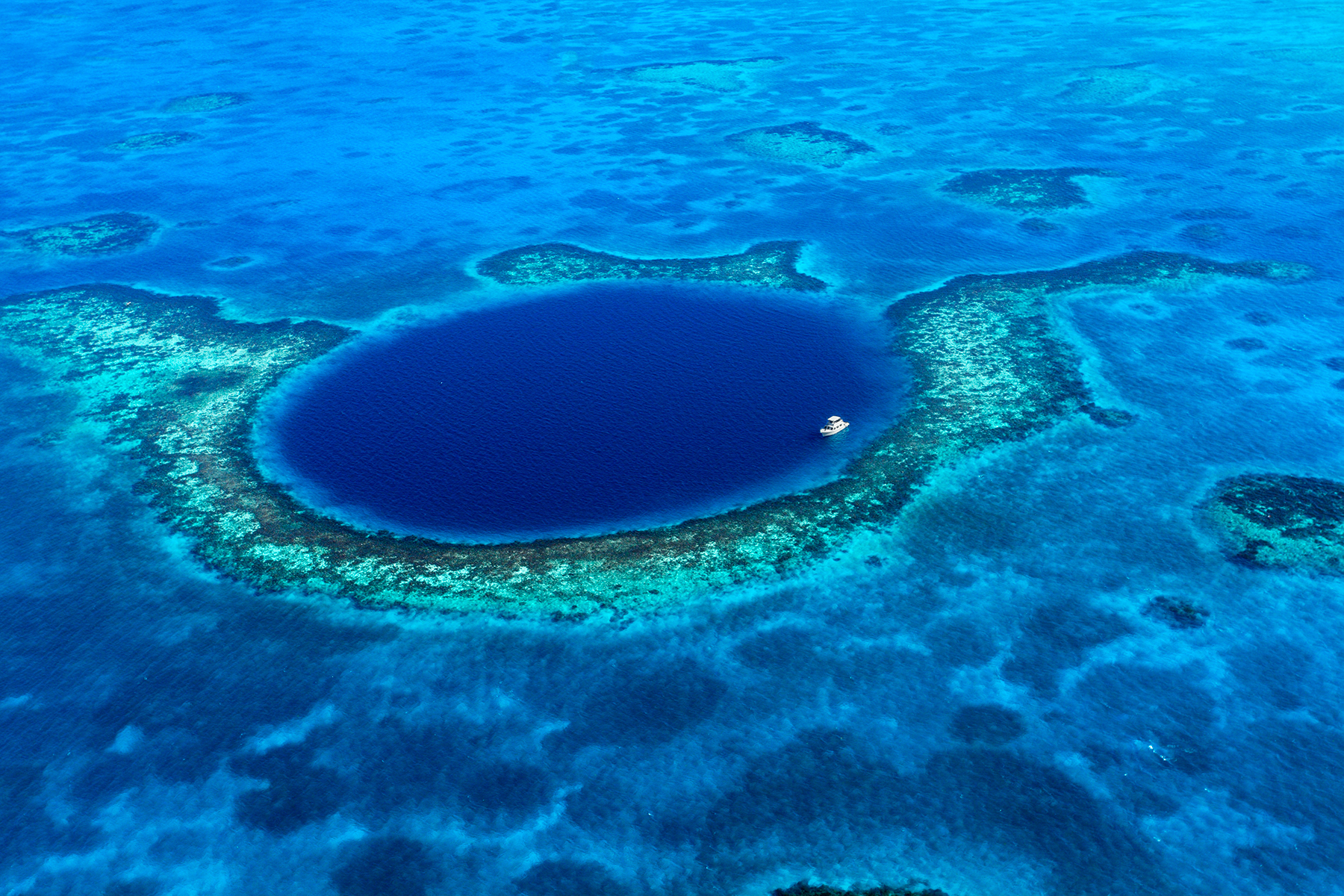 An aerial view of a boat moored in the Great Blue Hole off the coast of Belize