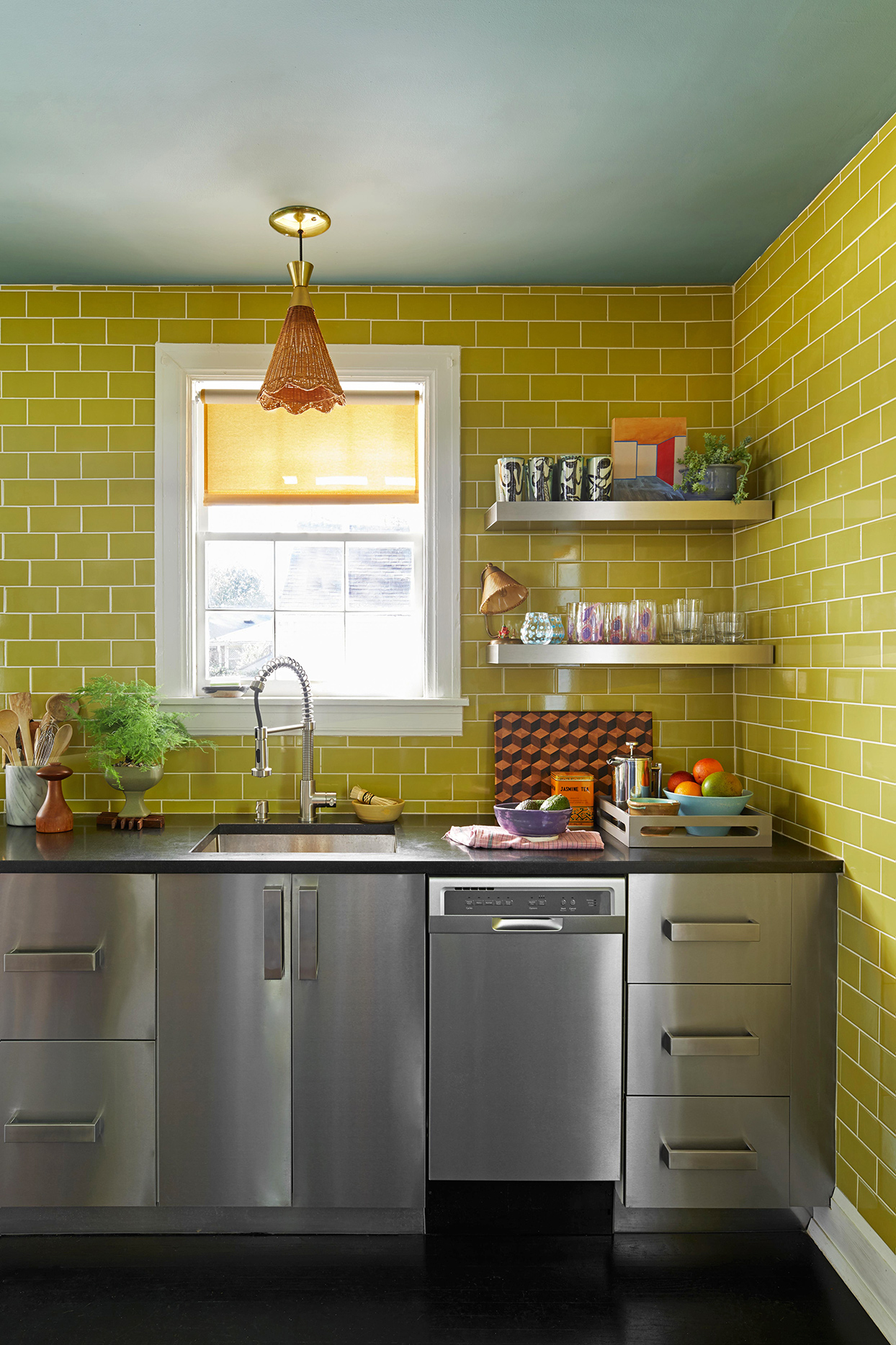 stainless steel kitchen with chartreuse subway tile on walls