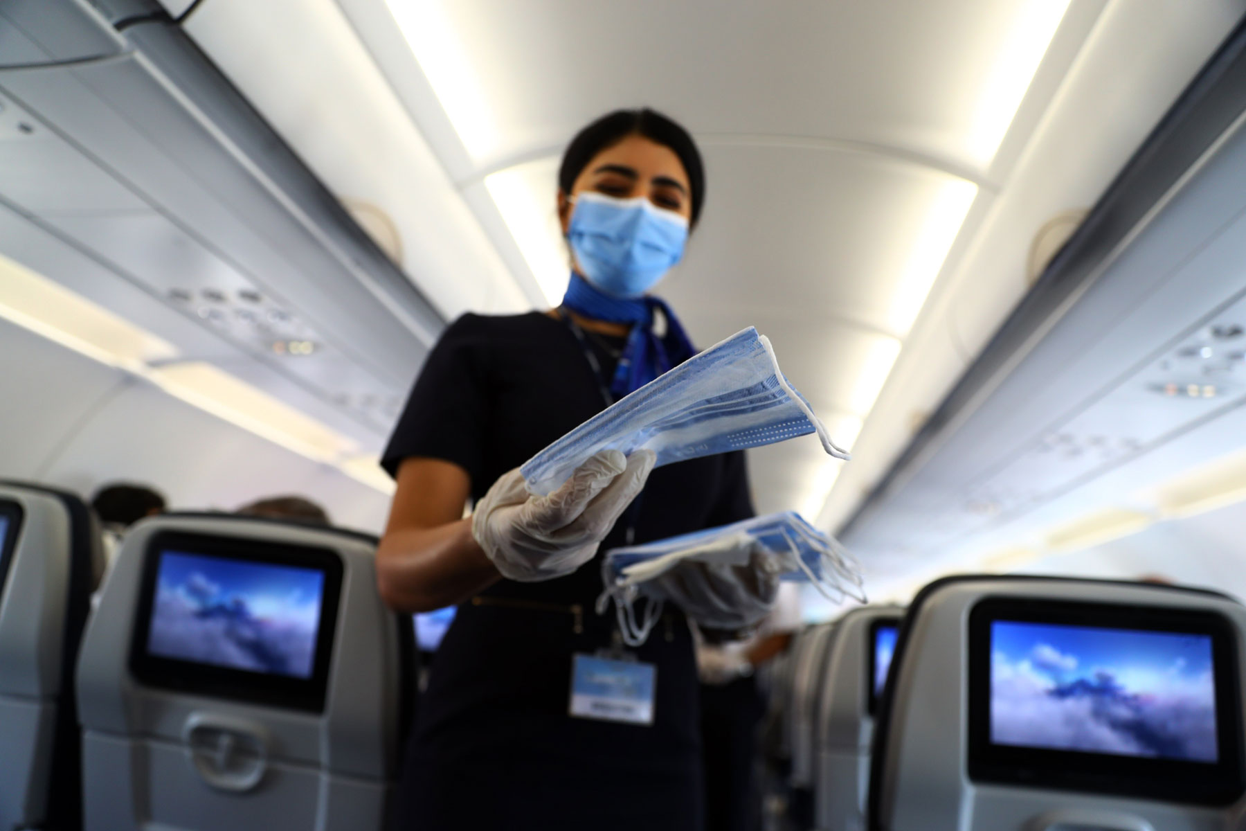 flight attendant face masks to passengers on an airplane