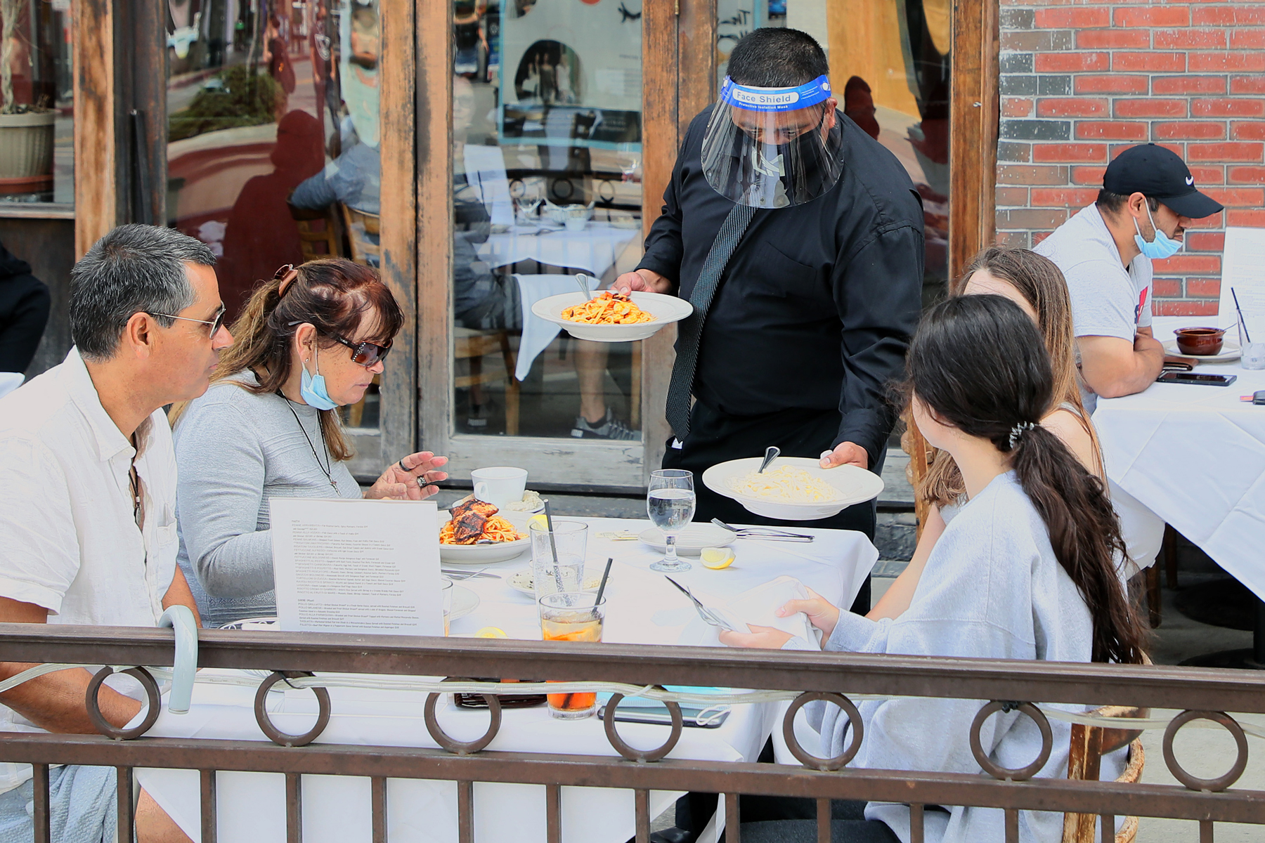 dining patrons being served by a waiter wearing a face mask and shield