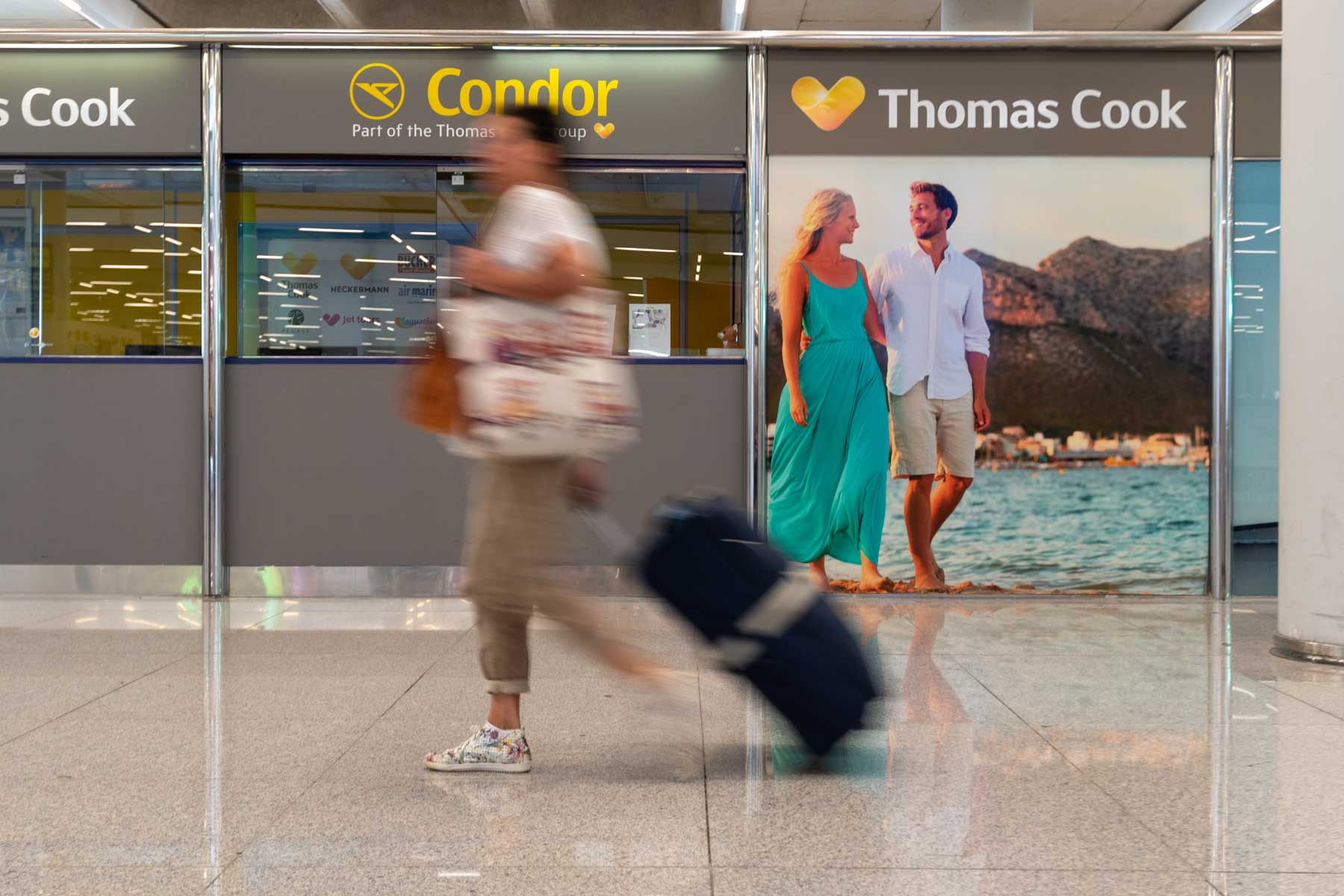A woman walks past an office of Condor and Thomas Cook at Palma de Mallorca airport.