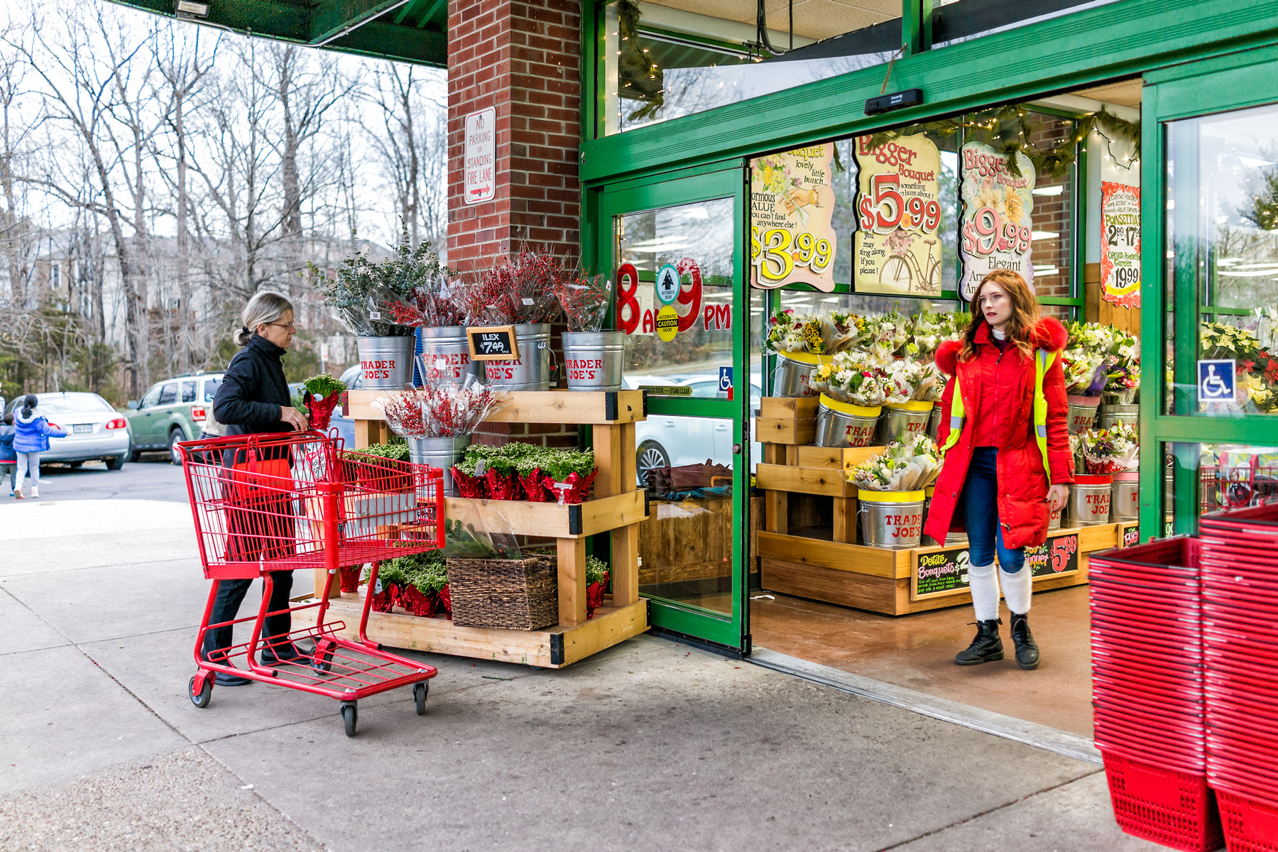 Trader Joe's employee in red clothes with customer, trolley shopping carts by store entrance doors outside women, winter flower pots, gardening plants in Virginia
