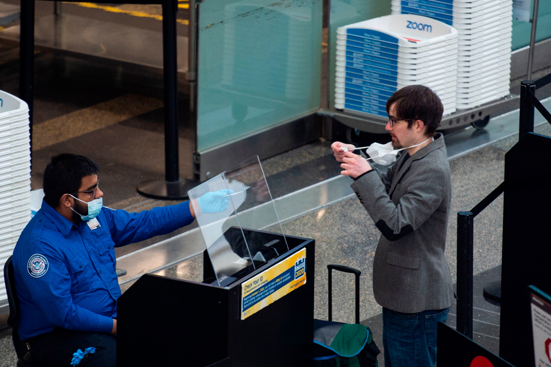 A passenger removes his mask as he has his ID checked by a Transportation Security Administration
