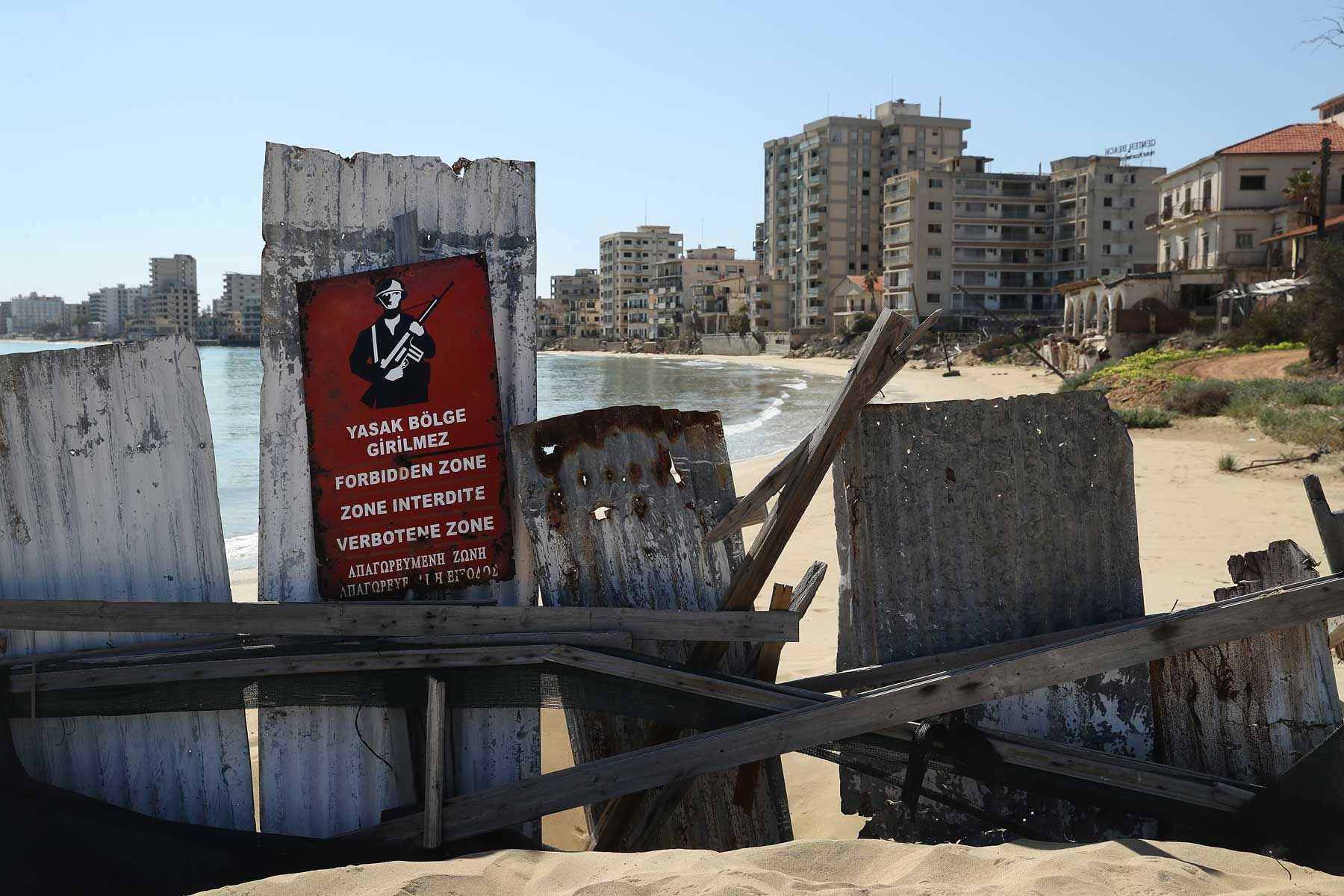 """Former, decaying hotel buildings stand beyond a makeshift barrier and a Turkish military sign inside the """"Forbidden Zone"""" of Varosha district on March 6, 2017 in Famagusta, Cyprus."""