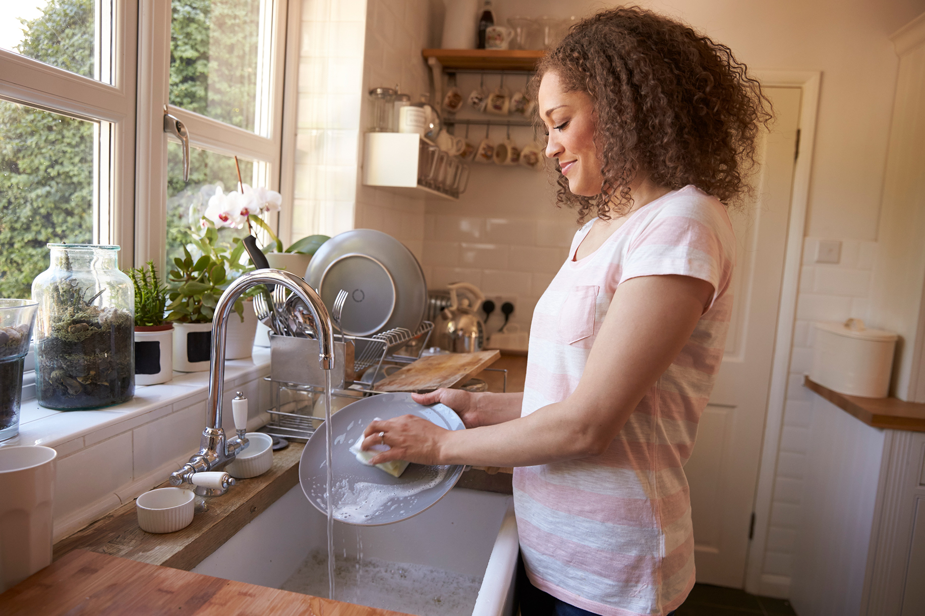 Person washing dishes at sink