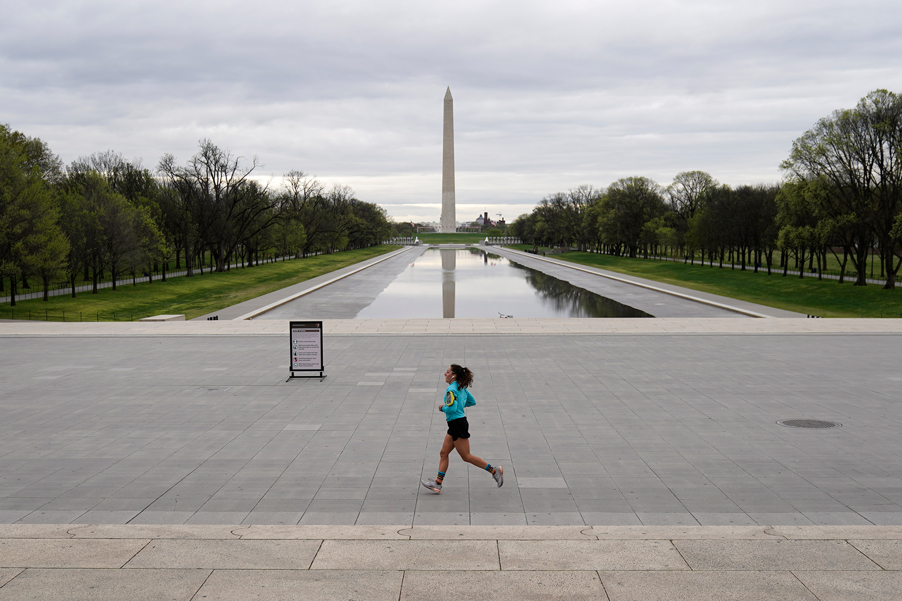 A woman jogs along a mostly empty National Mall during covid stay-at-home order in Washington, DC.
