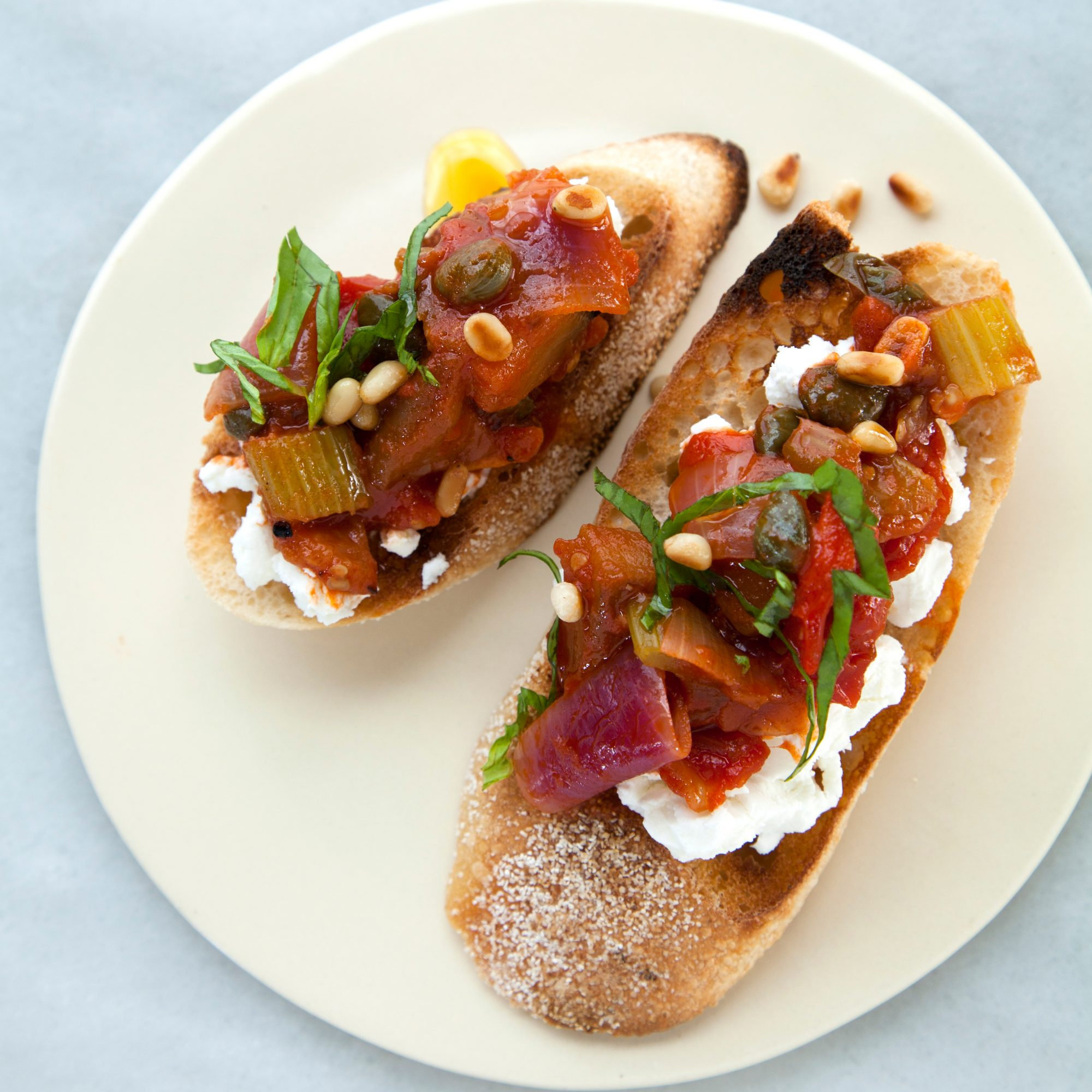 Caponata Crostini with Goat Cheese and Toasted Pine Nuts