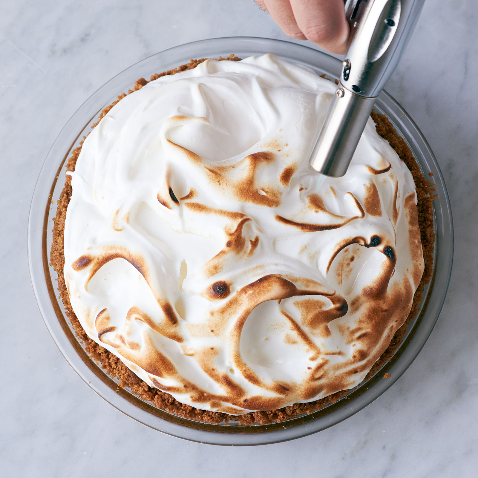 Browning the meringue with a blowtorch