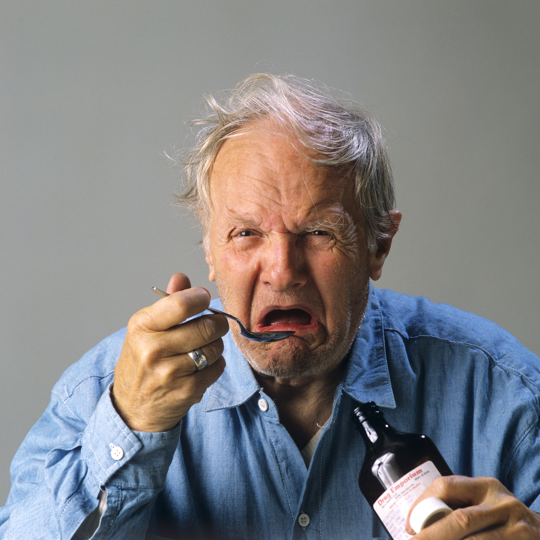 Old man taking cough syrup
