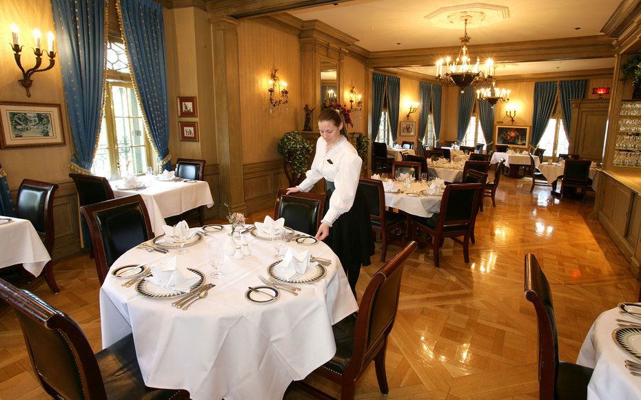 Lisa Solt, a server with 8 years of Disney experience serving customers, puts the finishing touches on a table at Disneyland's private Club 33.