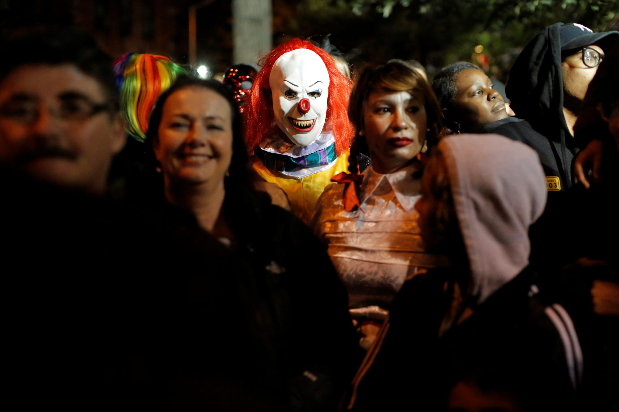 A person dressed in a clown costume stands amongst attendees during the Greenwich Village Halloween Parade in Manhattan, New York, U.S.