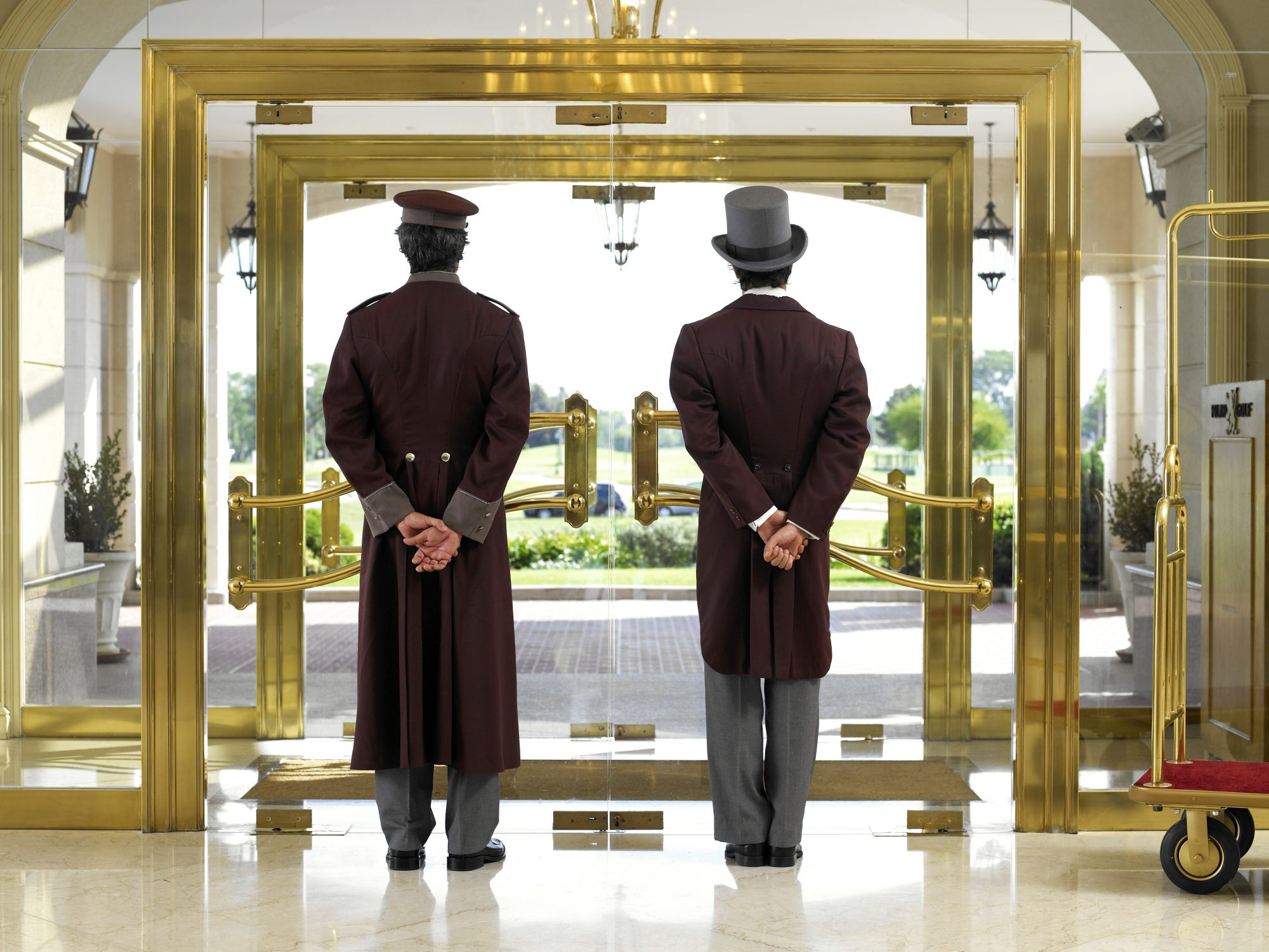 Concierge and bellboy standing at hotel entrance