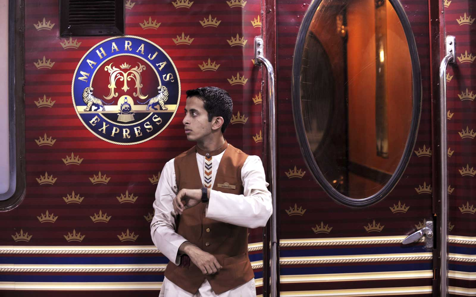 "An Indian railway assistant checks his watch as he stands beside the ""Maharajas' Express"", India's first pan-India super luxury train, prior to its departure for Delhi from Kolkata on March 20, 2010."